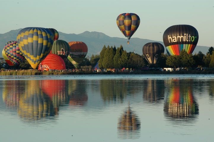 Several balloons floating over their reflections in a lake in Hamilton, New Zealand