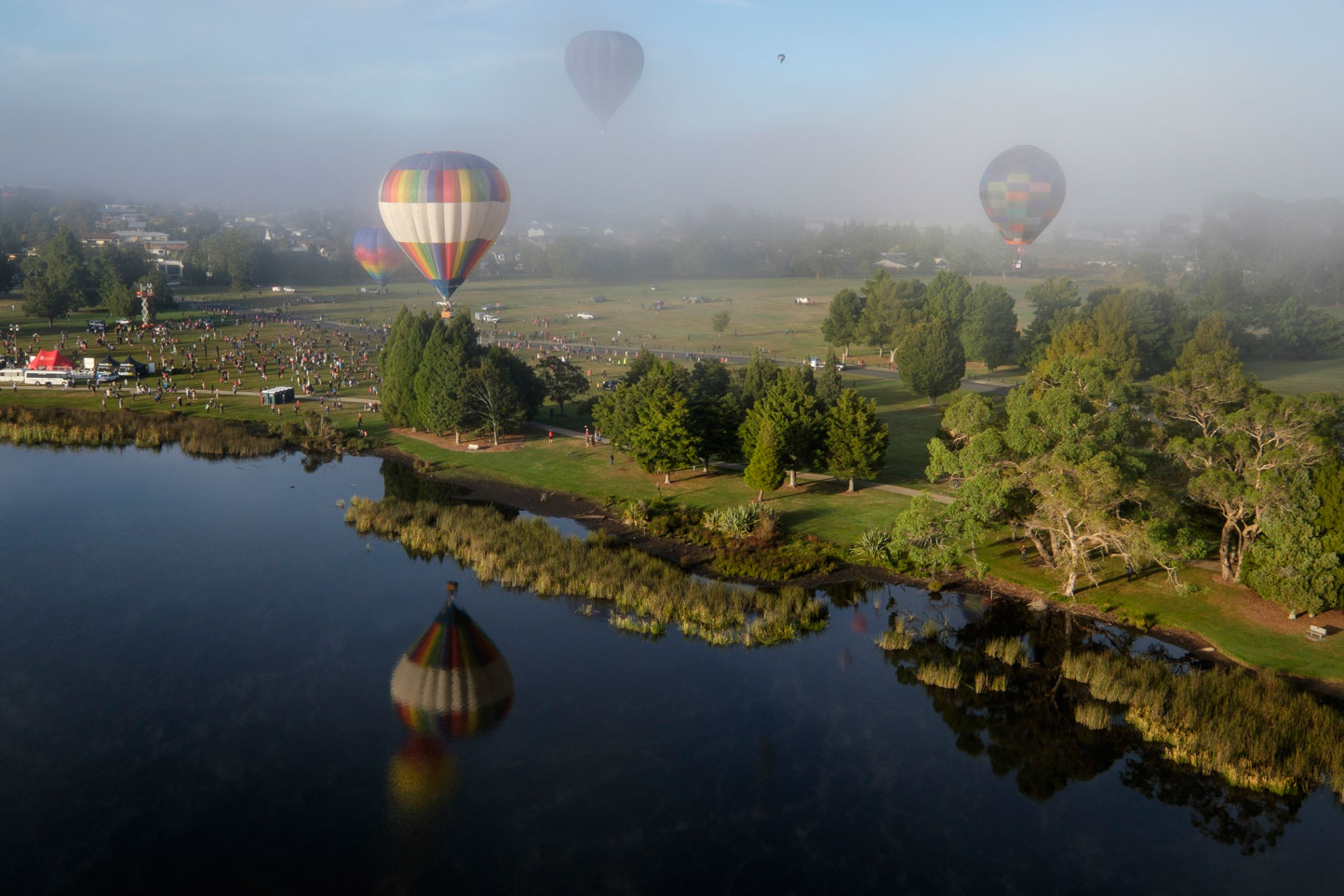 Balloons floating over a lake on a misty morning at Hamilton's Balloons Over Waikato, New Zealand