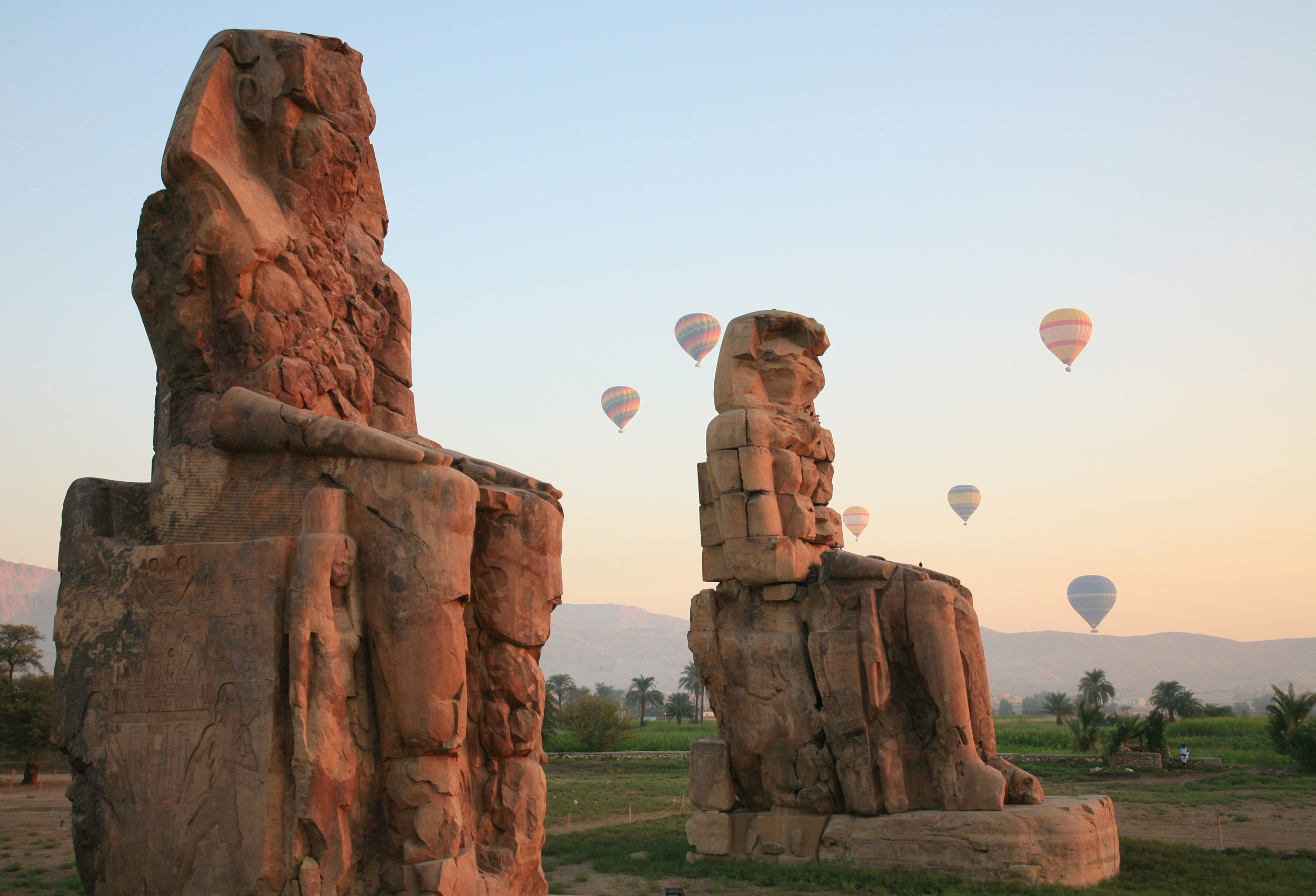 Two colossal seated red stone statues with hot air balloons floating in the background at Luxor