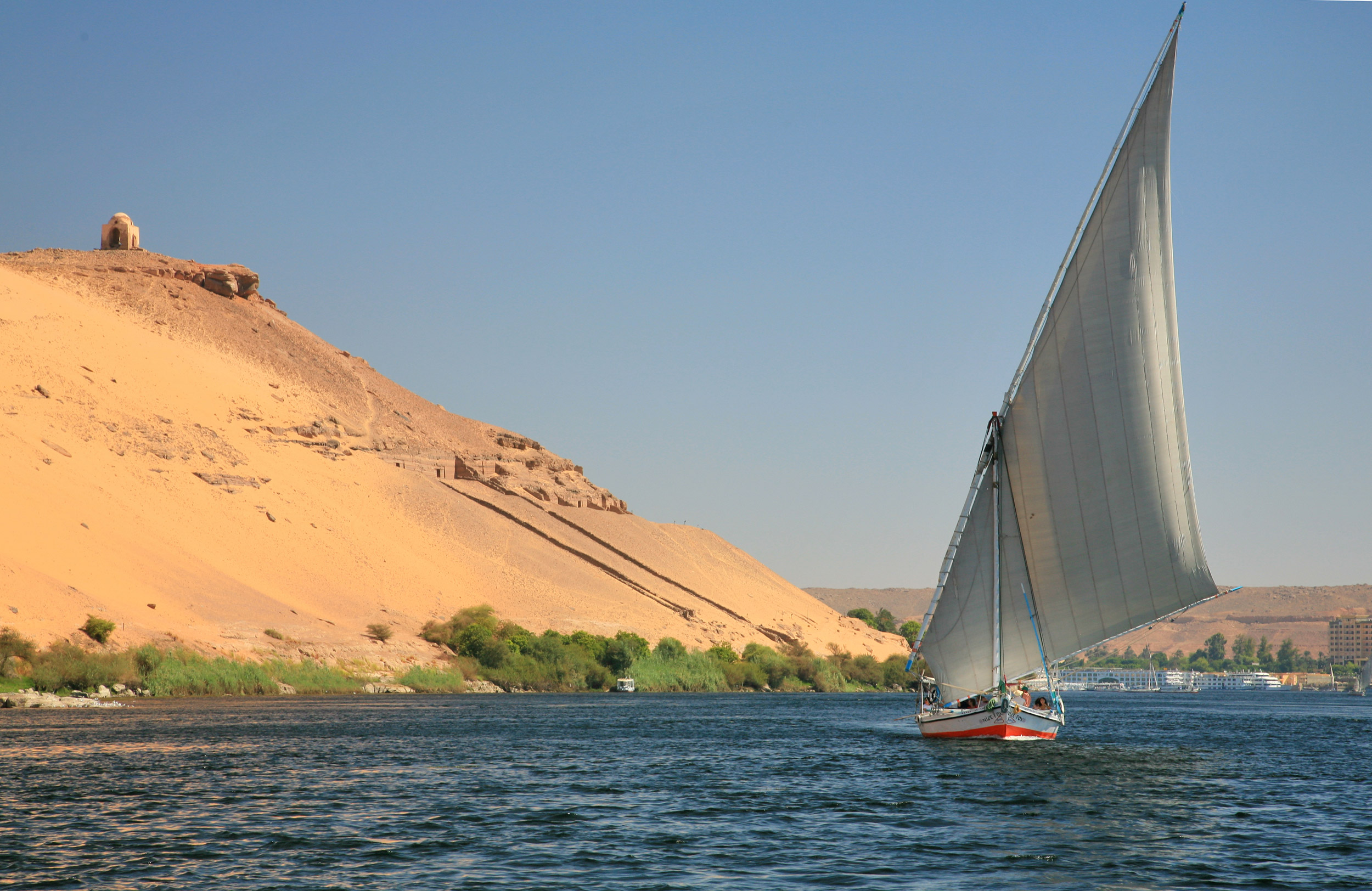A skiff on the River Nile with a steep brown hill on the side in Egypt