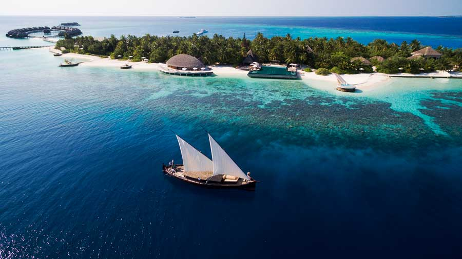 A dhoni sailing past an island resort nestled in a very blue sea, Maldives