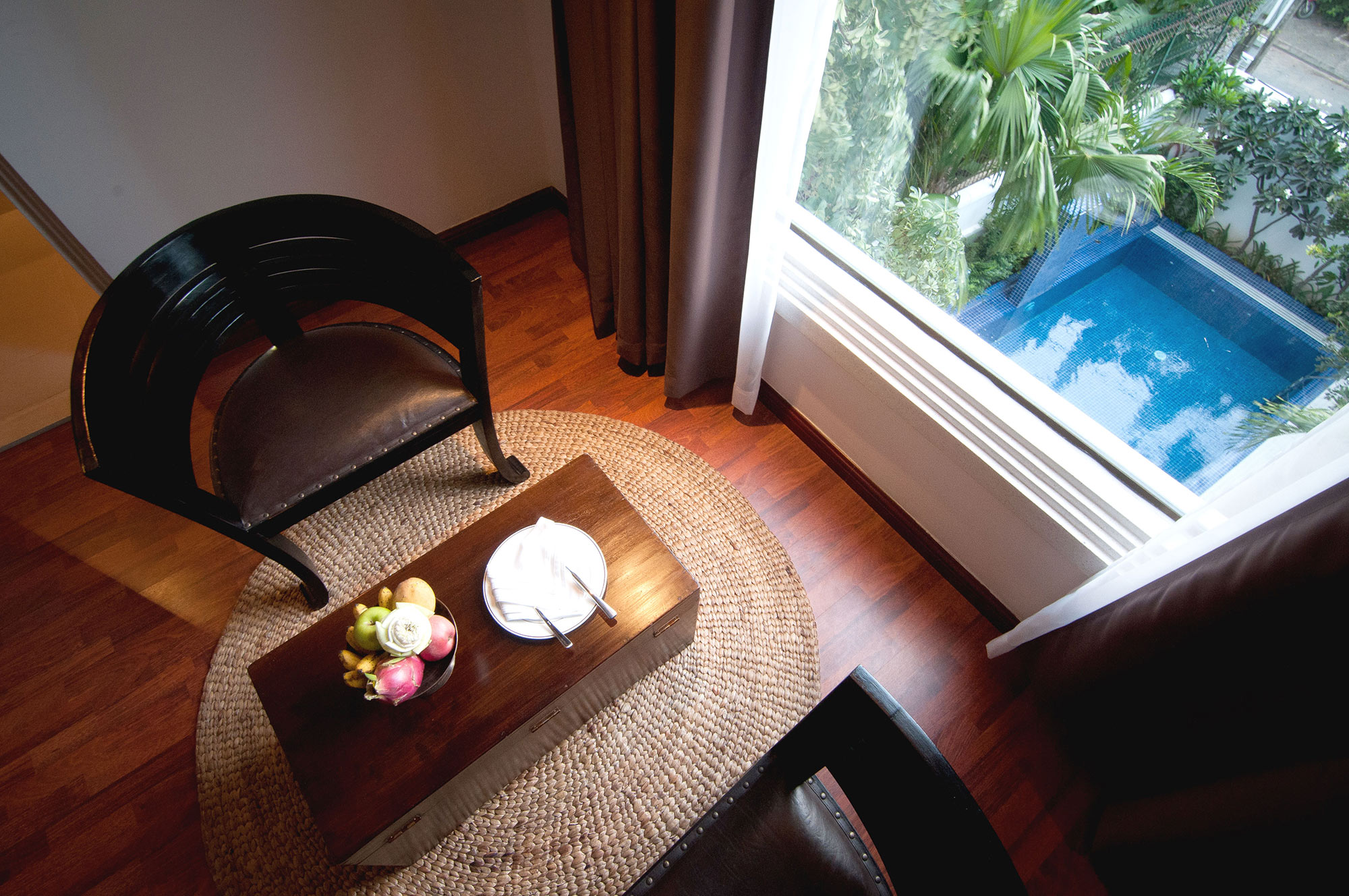 A chair and table by a window overlooking a pool at La Rose Suites, Phnom Penh's first 5-star boutique hotel, Cambodia
