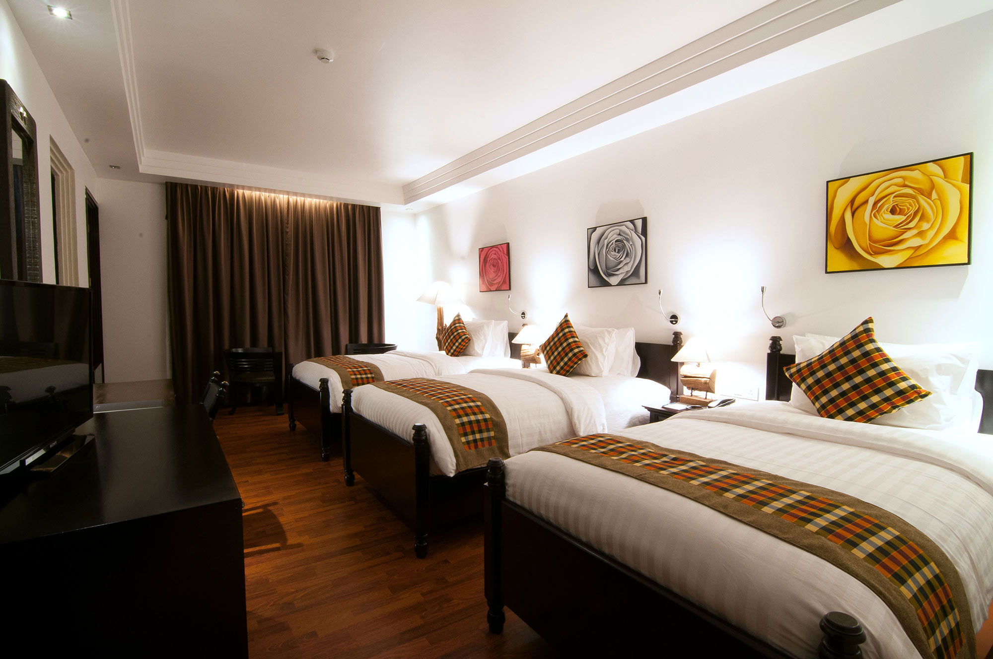 A bedroom suite with three beds along a wall at La Rose Suites, Phnom Penh's first 5-star boutique hotel, Cambodia