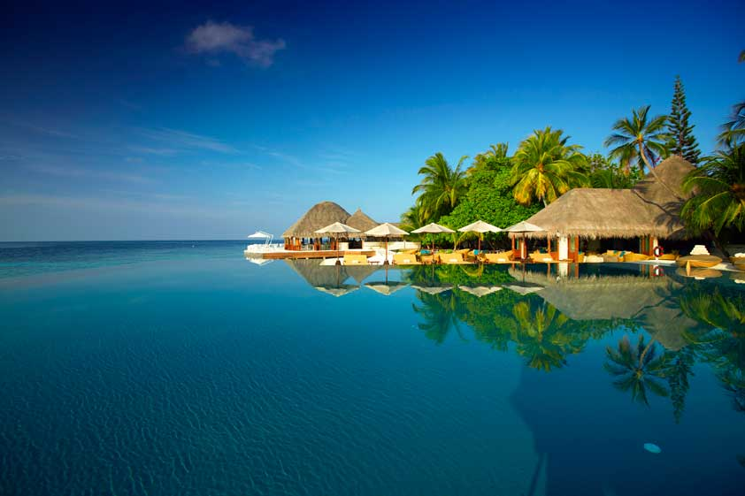 Umbrellas and huts reflecting into the infinity pool with a view onto the ocean