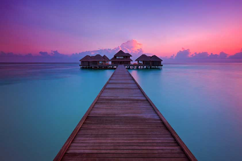 Long wooden boardwalk through the ocean leading to the thatched buildings of the spa at sunset, Maldives