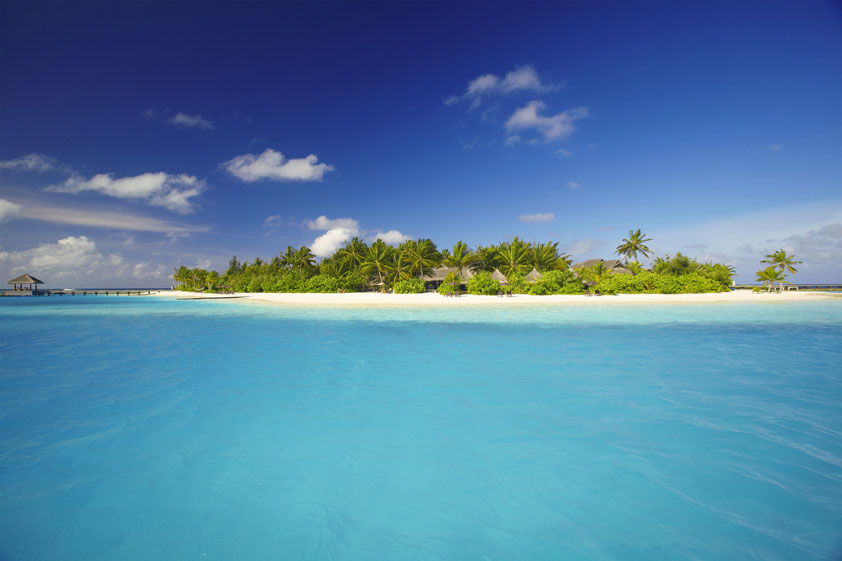 Looking across blue water to a green lush island with the thatched roofs of a resort nestled in the trees