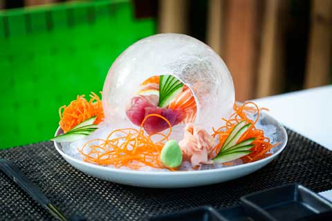Tuna and salmon encased in a transparent crackled globe in ice on a plate with carrot curls and cut vegetables around it, Niyama, Maldives