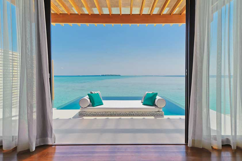 View through curtains onto a divan overlooking an infinity pool and and the ocean in the distance, Niyama, Maldives