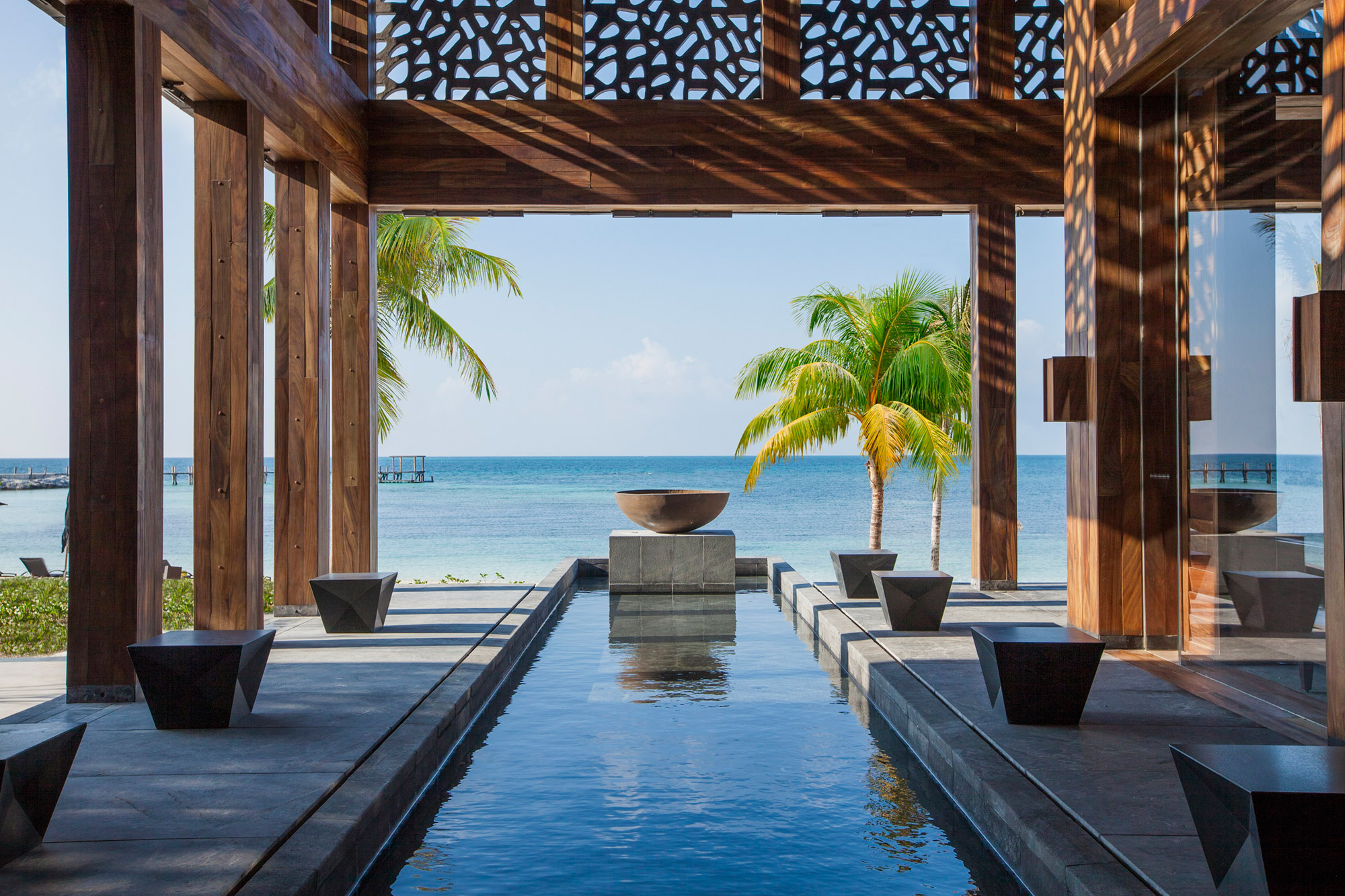 View over a channel water feature amongst wooden pillars out to palms and the sea