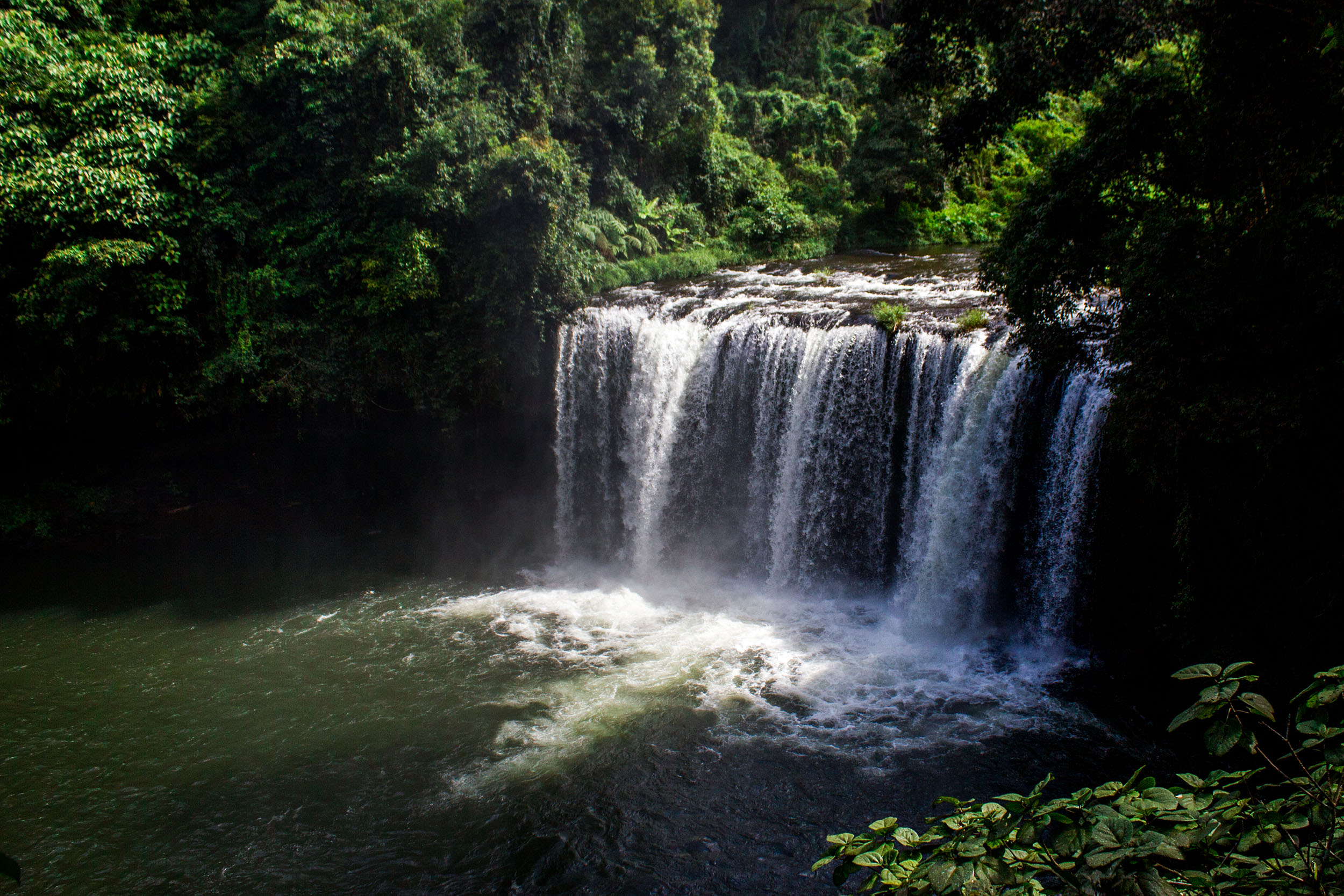 A medium sized waterfall cascading into the river, Bolaven Plateau, Laos