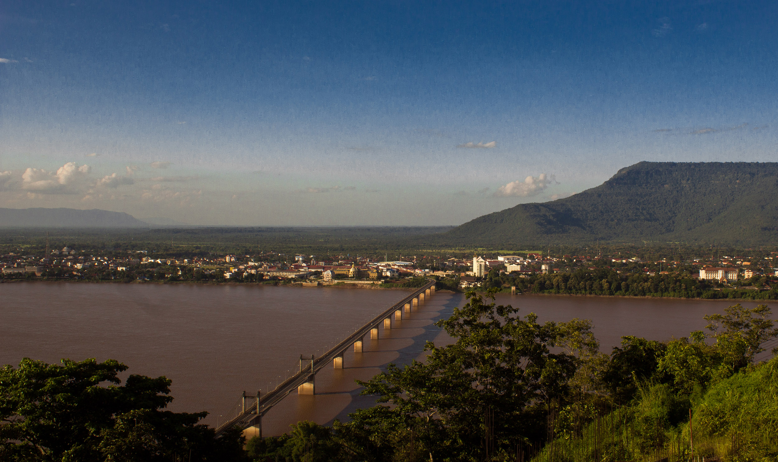 Dusk shot of a long bridge over the river to a lighted town with a mountain in the background, Laos