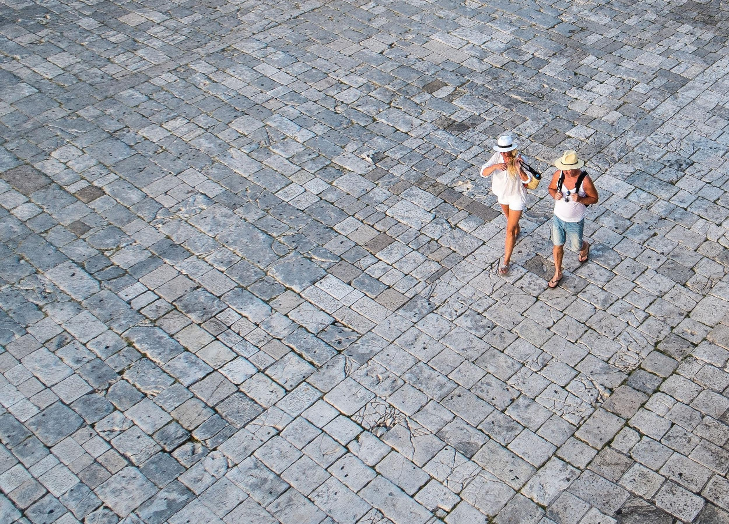 A couple in shorts and hats crossing stone paving in Hvar, Croatia.