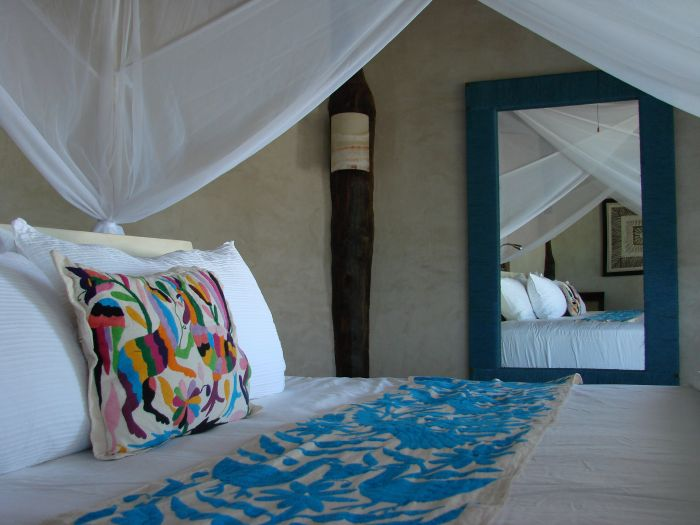A wooden bed with mosquito nets, traditional embroidery and fresh white linens reflecting in a mirror at Encantada Boutique Hotel in Tulum.