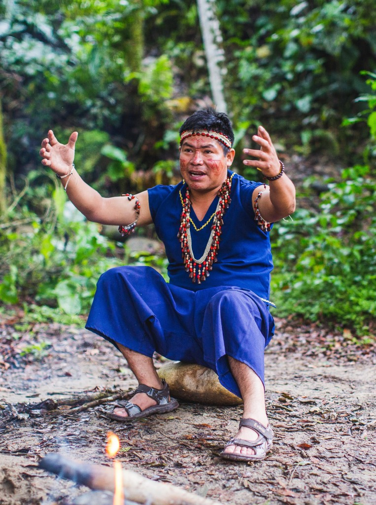 Man seated on a rock in blue clothes, arms raised and talking, Silverio Mamallacta, Runa.