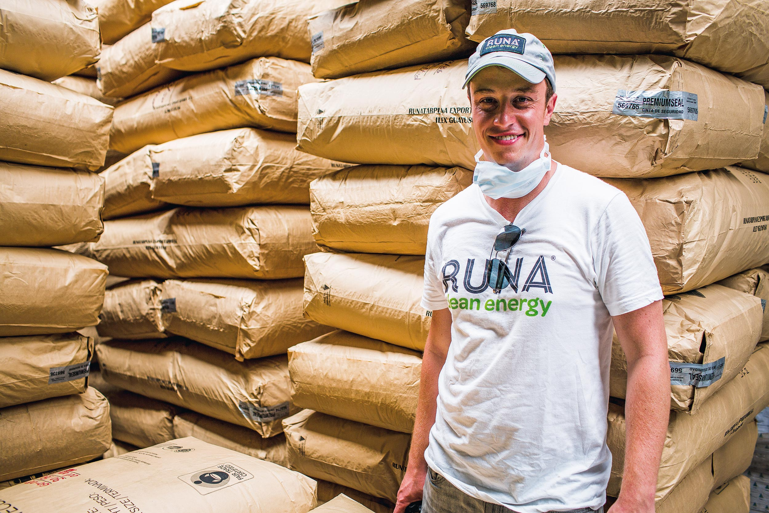 A smiling man leaning back against stacked sacks, Runa, Ecuador