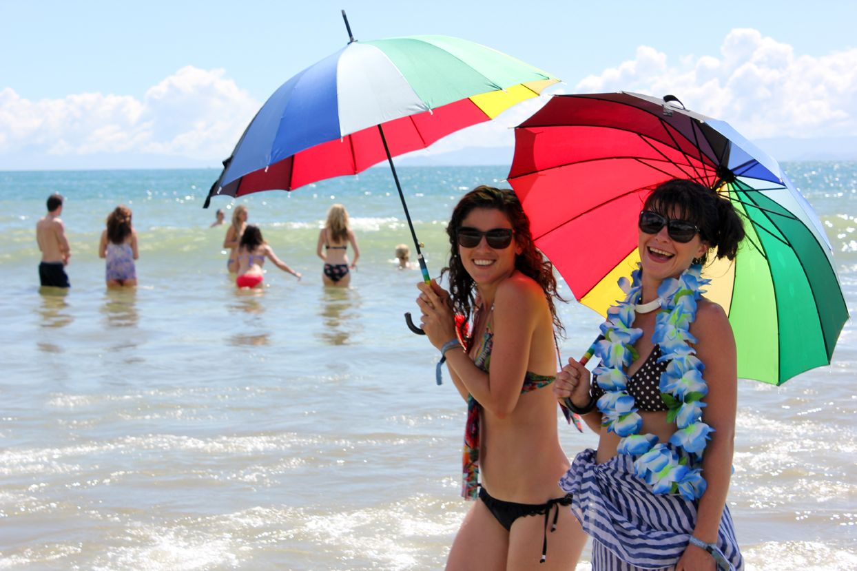 Girls in the sea with rainbow umbrellas