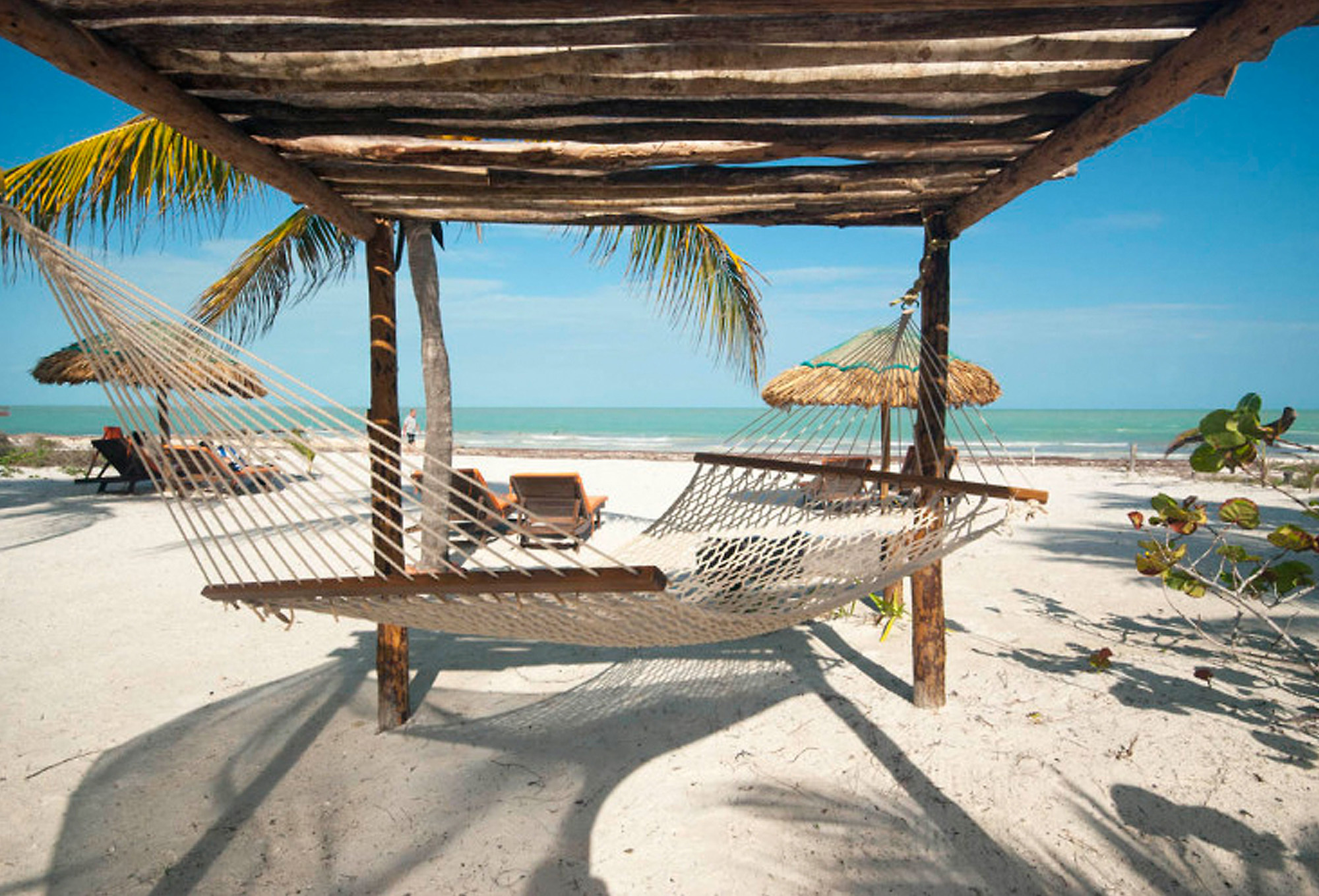 A hammock slung under shade looking out to the beach and sea at Hotel Zomay, Isla Holbox, Mexico