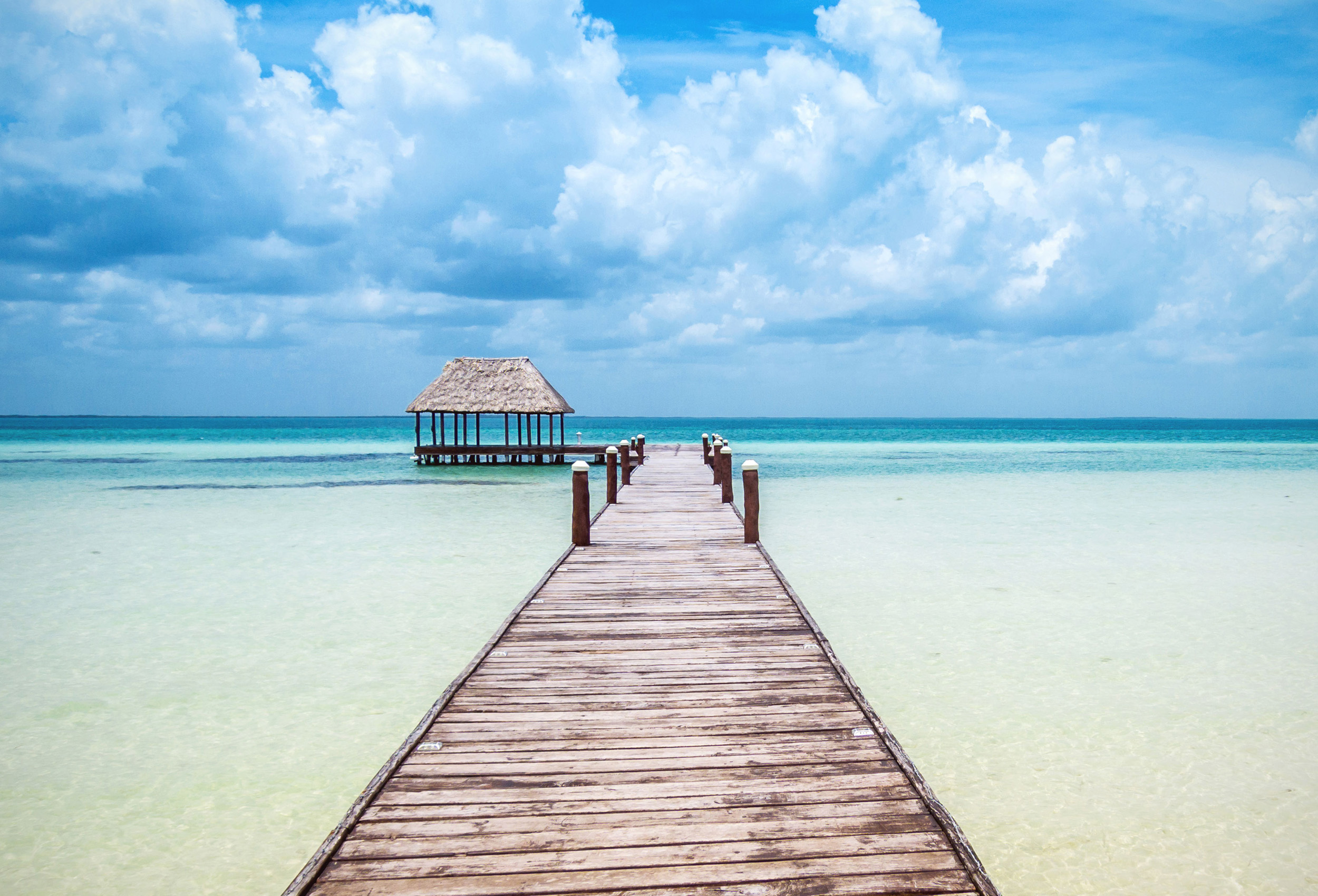 A long boardwalk pier extending into the blue sea at Holbox Island, Mexico.