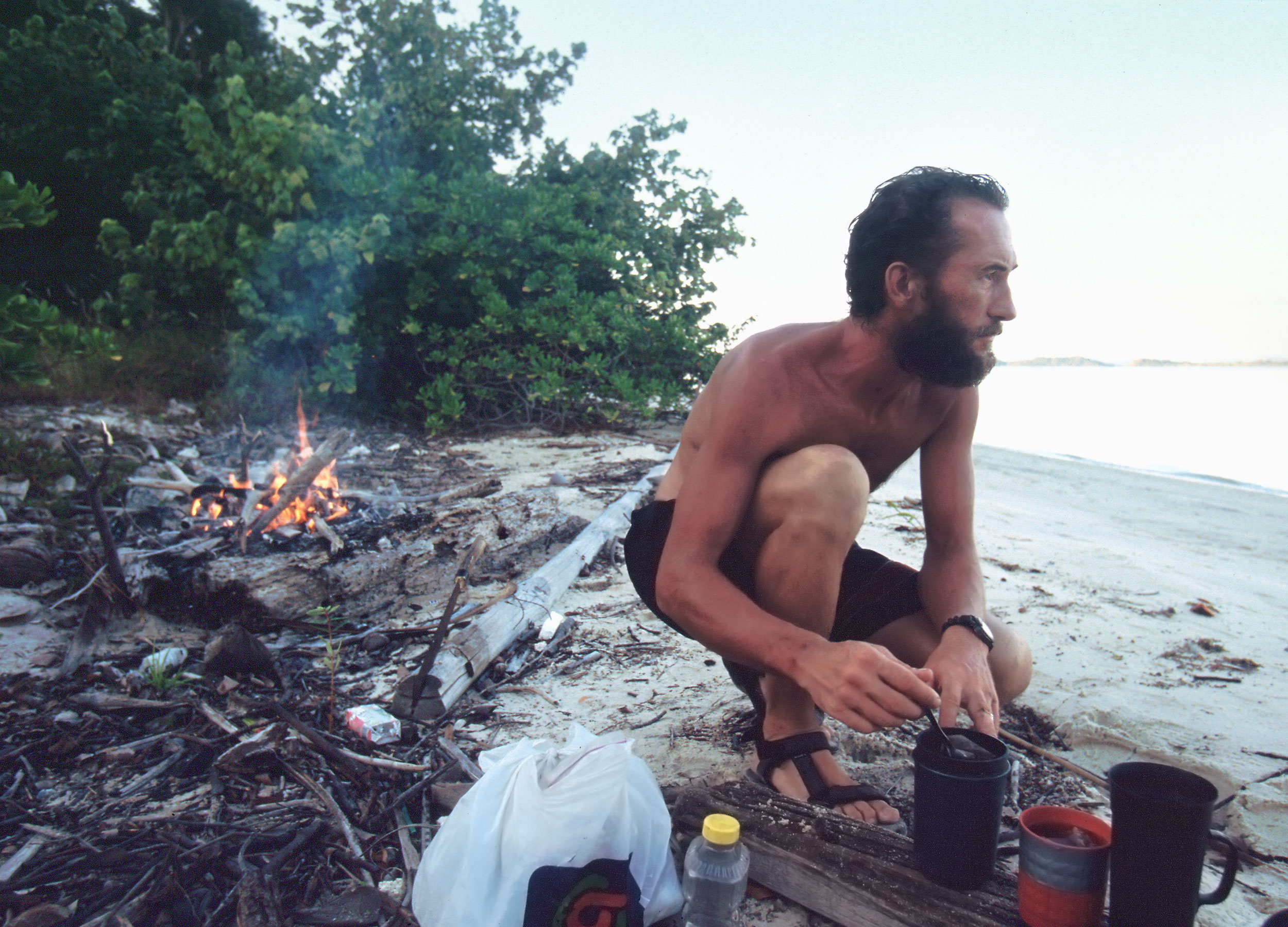 Man squatting by his campfire over cans by the water's edge