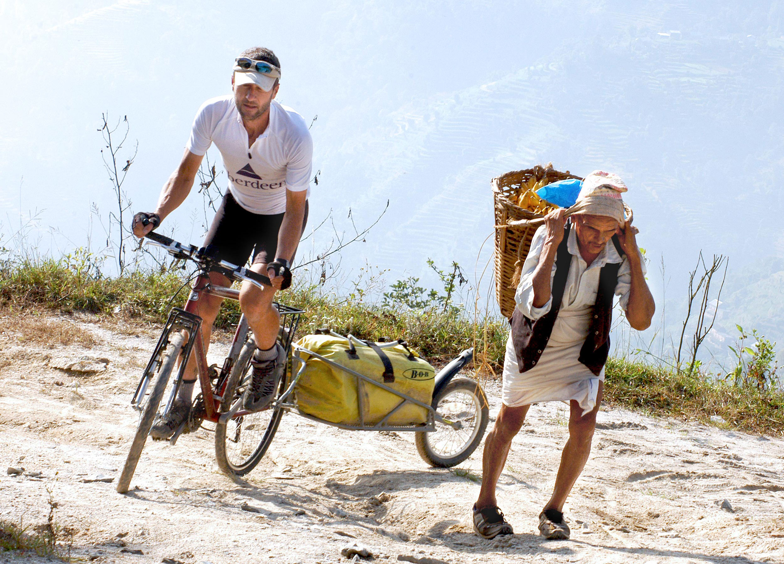 Man on a cycle with trailer going uphill past a Nepali man lugging a load in a wicker basket on his back