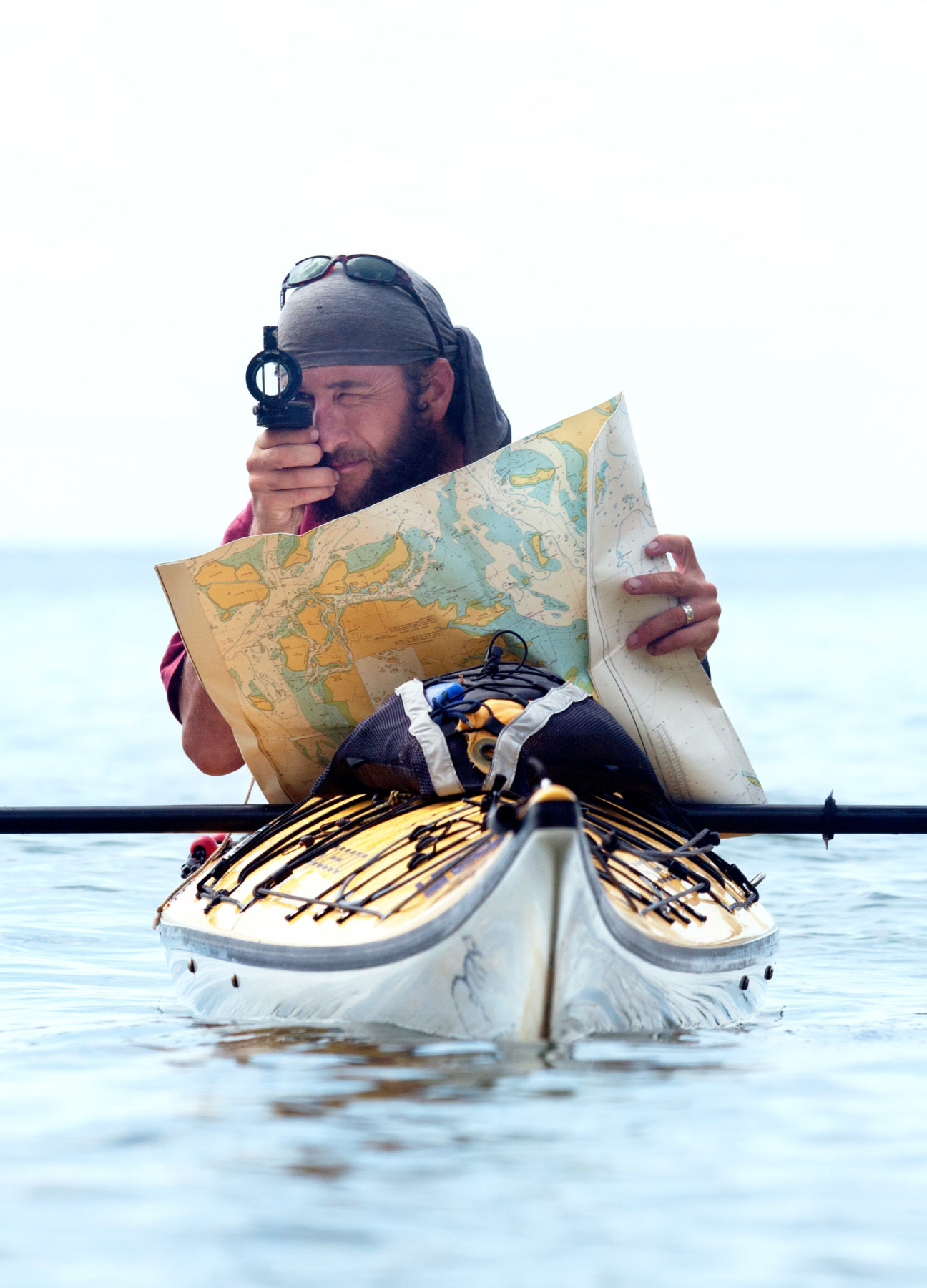 Man in a canoe holding a map and compass charting his course