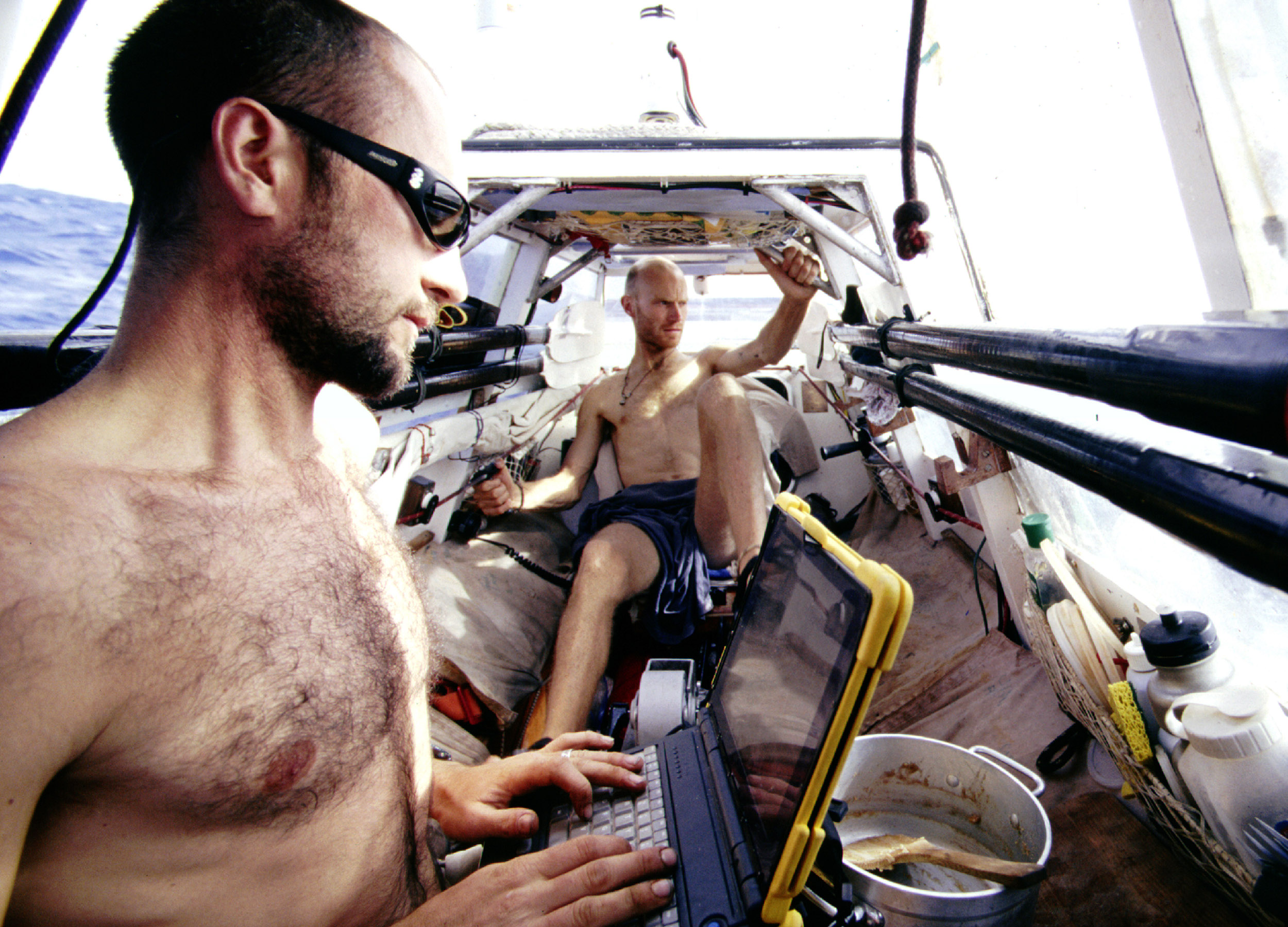 Two barechested men in a boat; one on a laptop, the other pedalling away