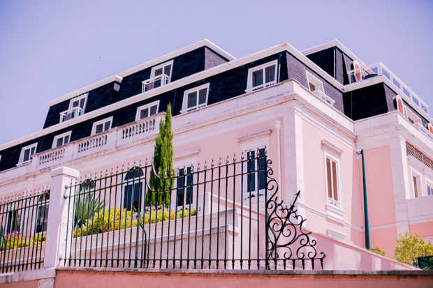 Front view of a pink and black building, the Lapa Palace Hotel