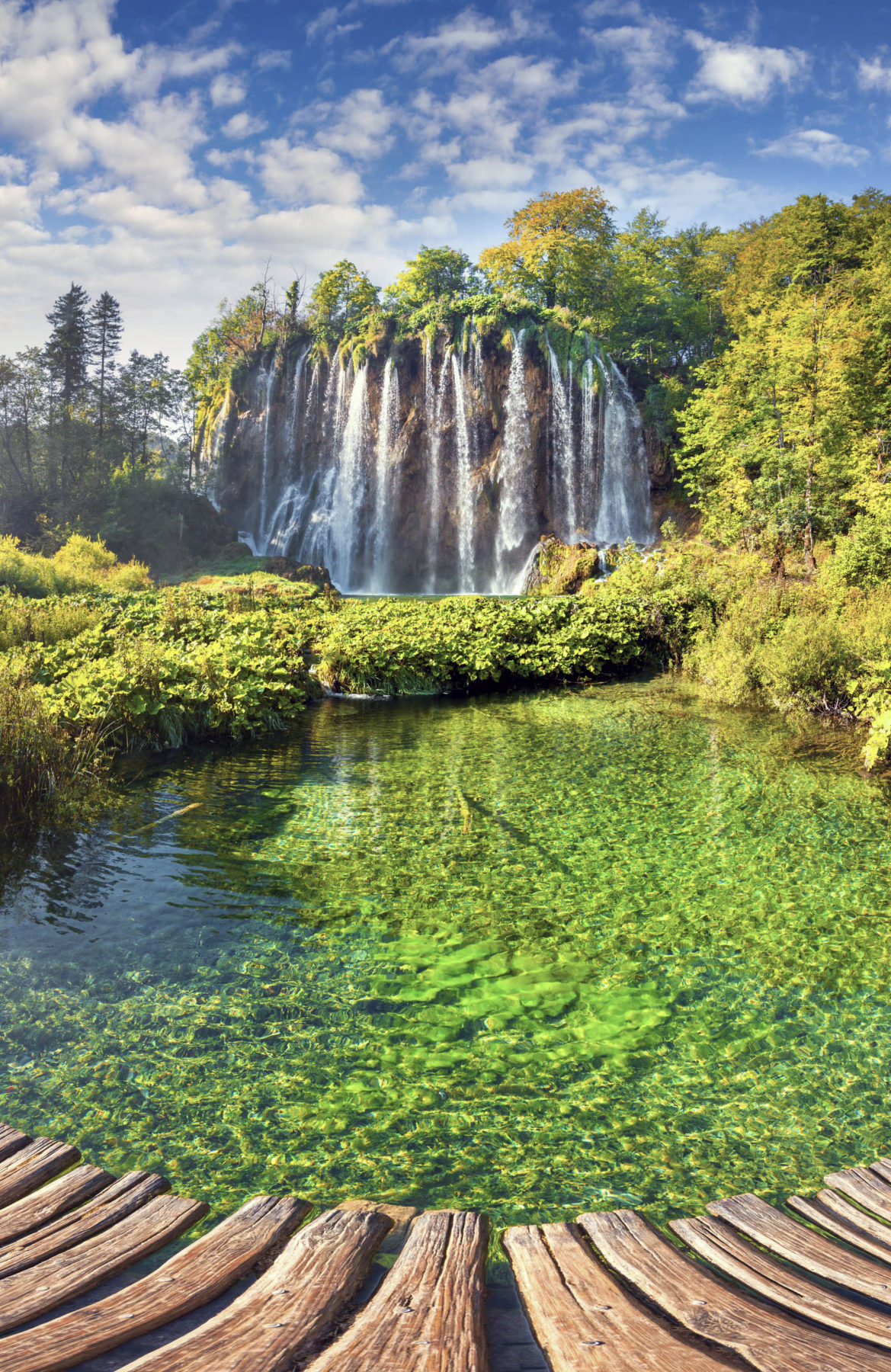 Falls cascading off a cliff into clear lakes at Plitvice Lakes National Park