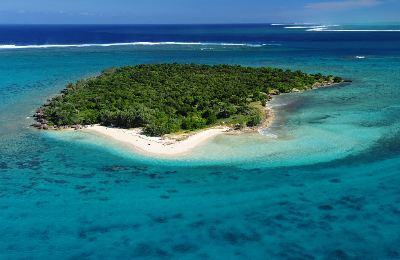 Aerial view of a wooded island with a small white sand beach in very blue sea, New Caledonia