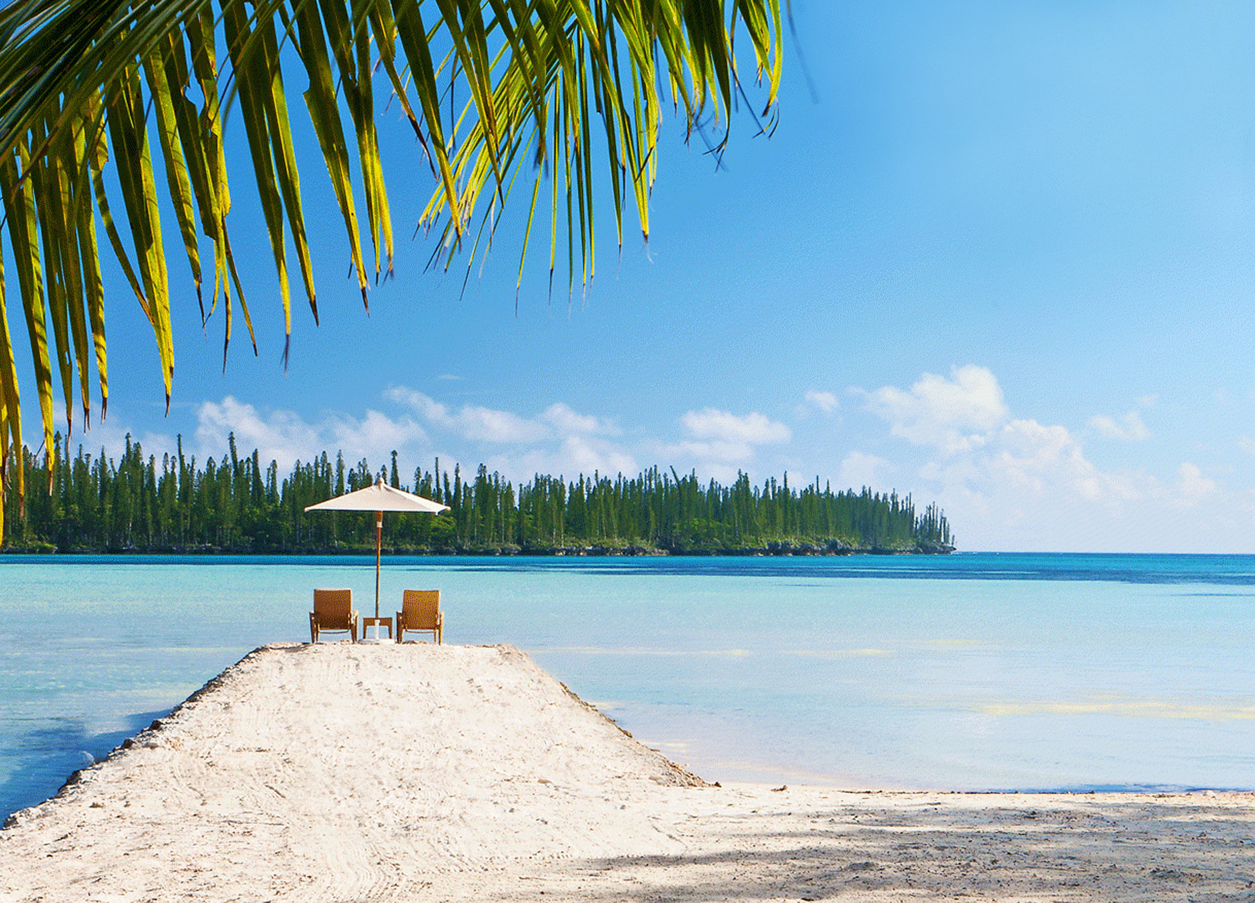 Two chairs under an umbrella on a sandspit looking out across the lagoon to a pine covered peninsula, New Caledonia