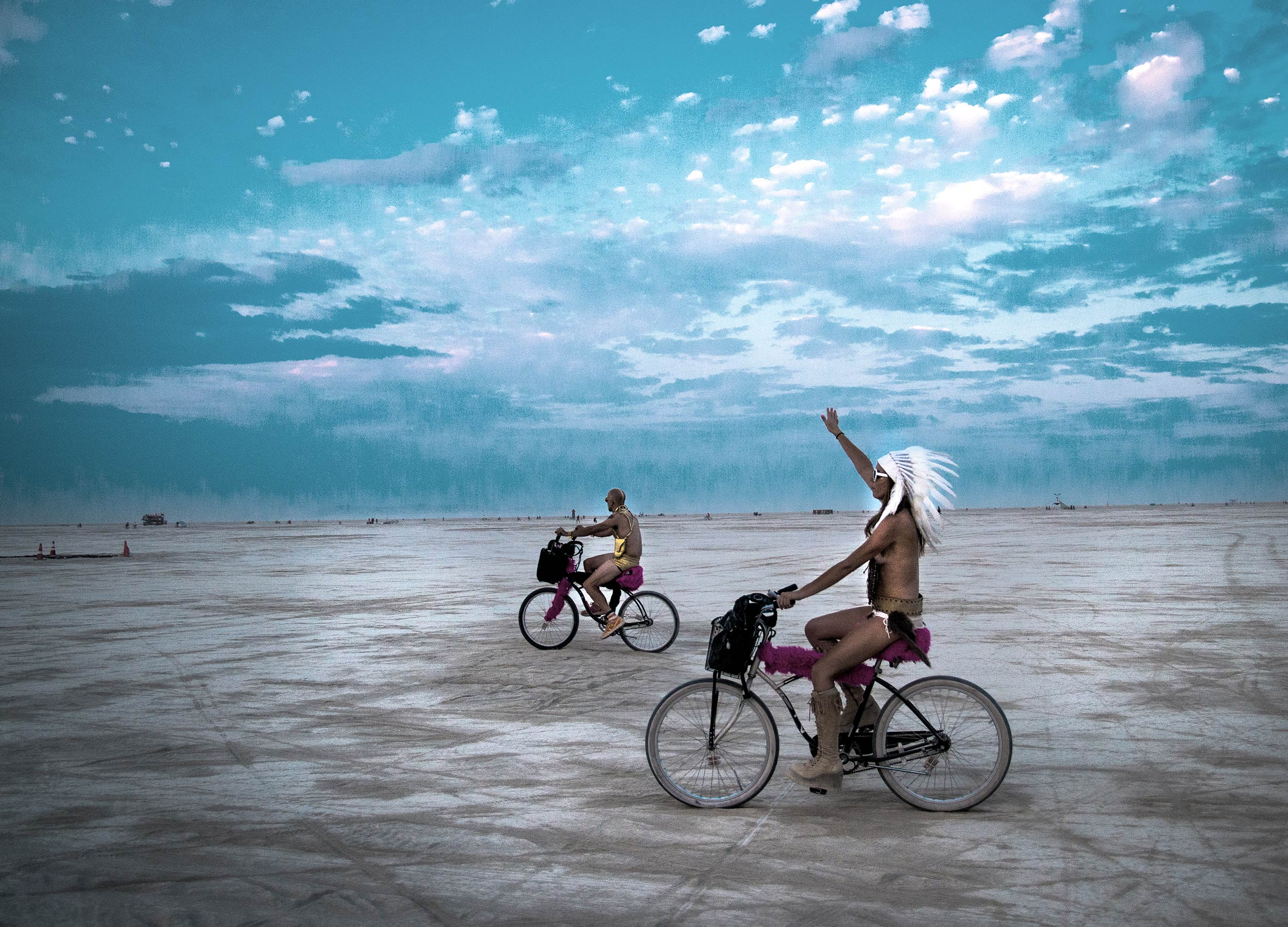 Two men in Red Indian costume cycling across the Nevada desert at Burning Man festival