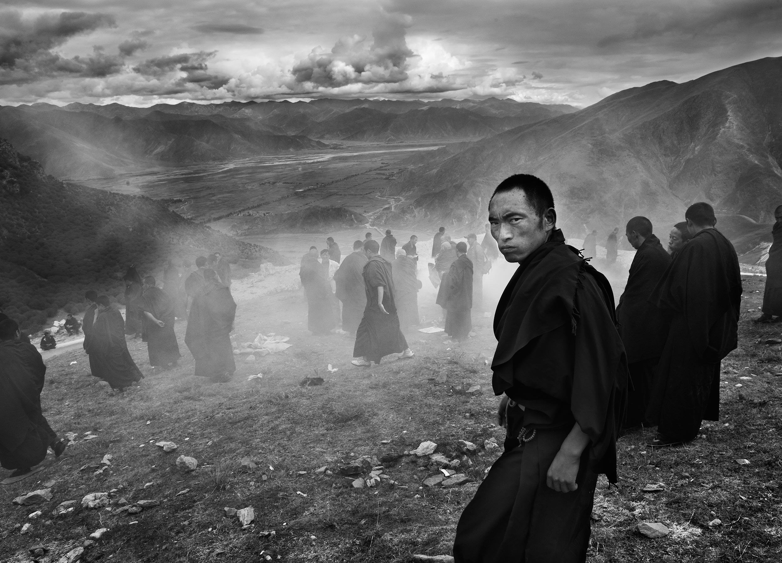 Buddhist monks walking down a misty rocky mountainside at Ganden university monastery, Tibet