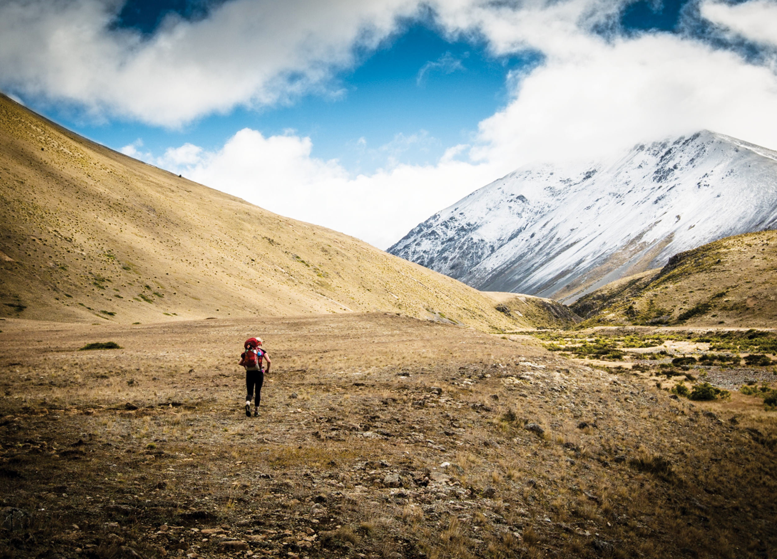 Woman with backpack traversing barren landscape with mountains ahead