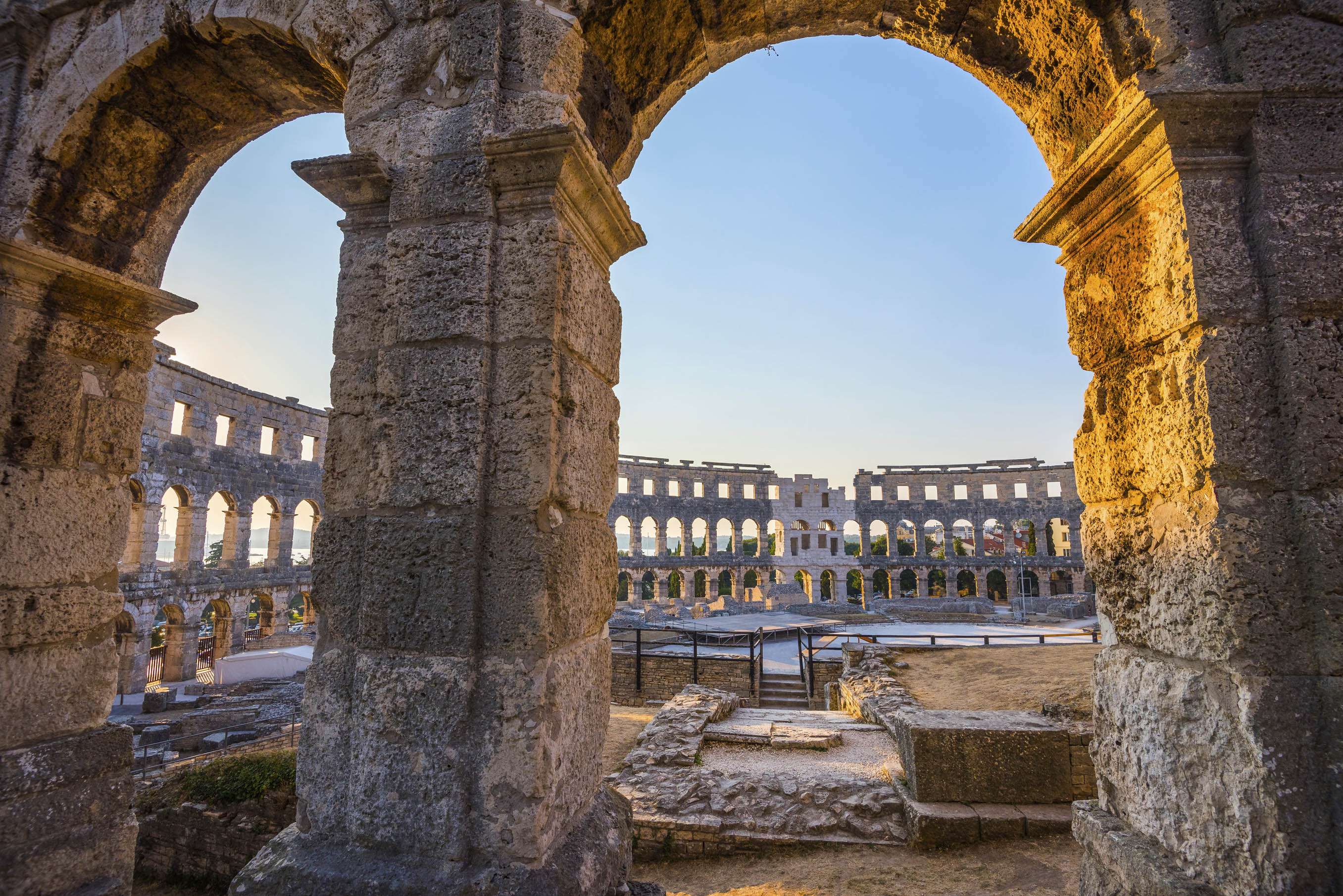 View through rounded arches touched by sun at the ampitheatre in Pula
