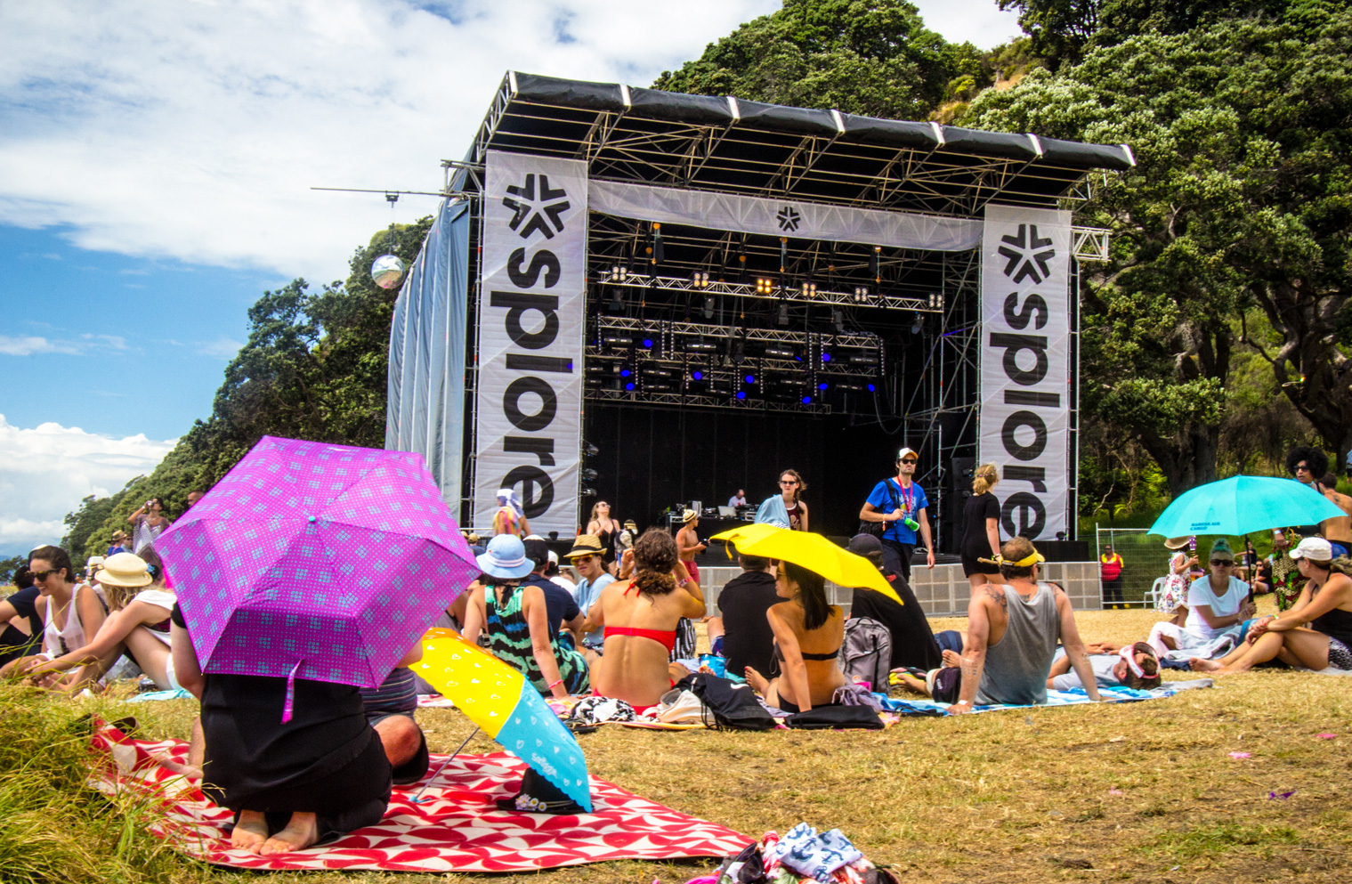 People sitting in the sun in front of the Splore stage