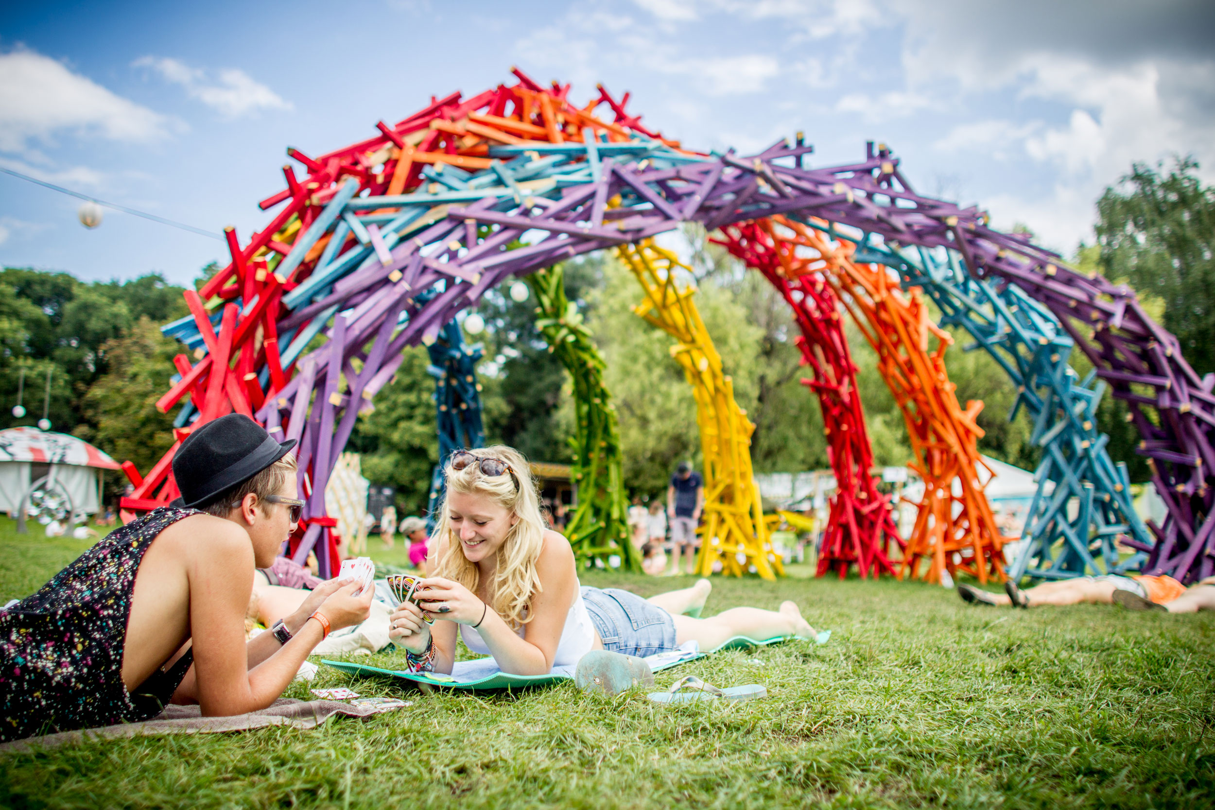 Friends relax under the rainbow sculpture at Sziget festival