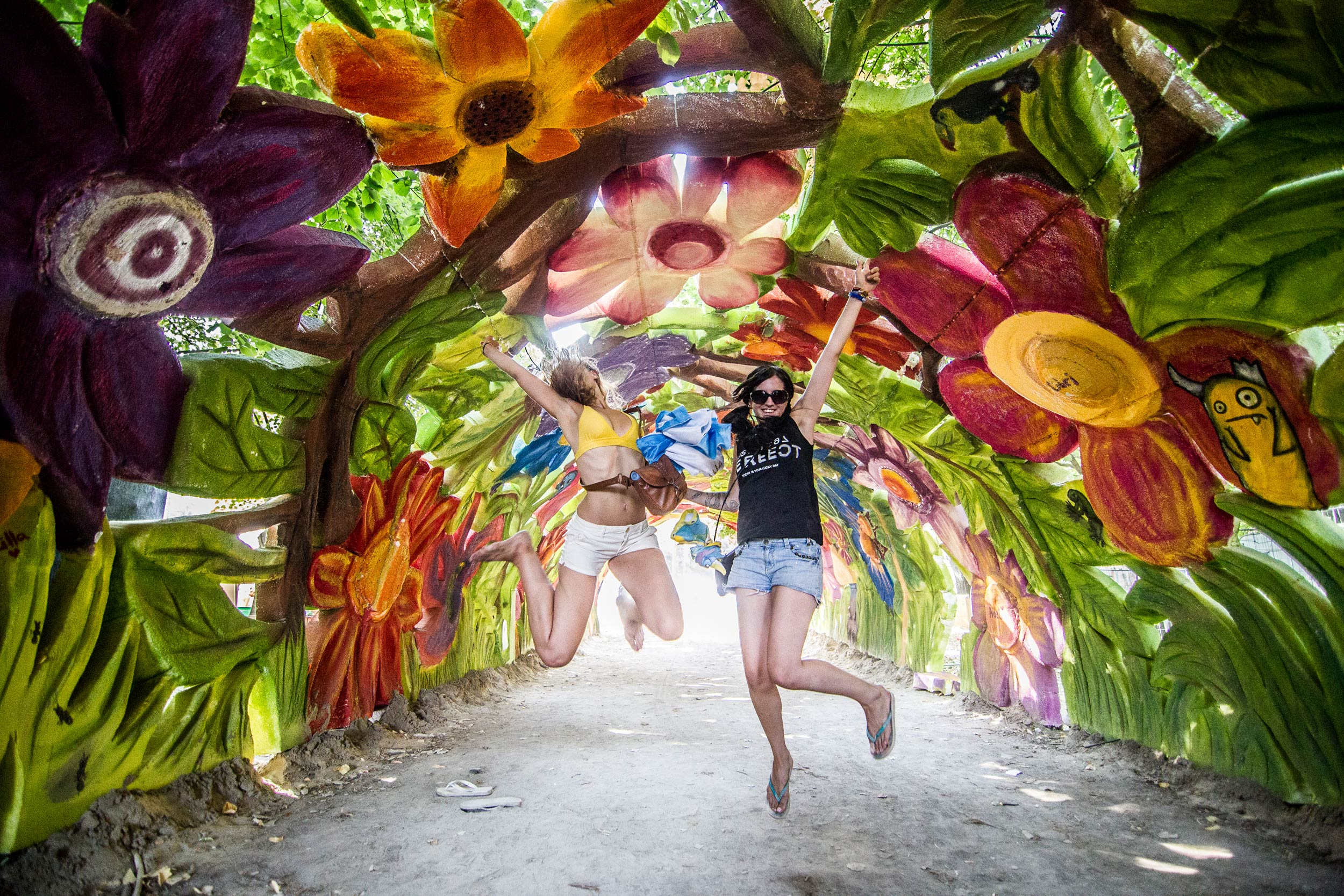 Girls jumping up in the air inside a Sziget sculpture