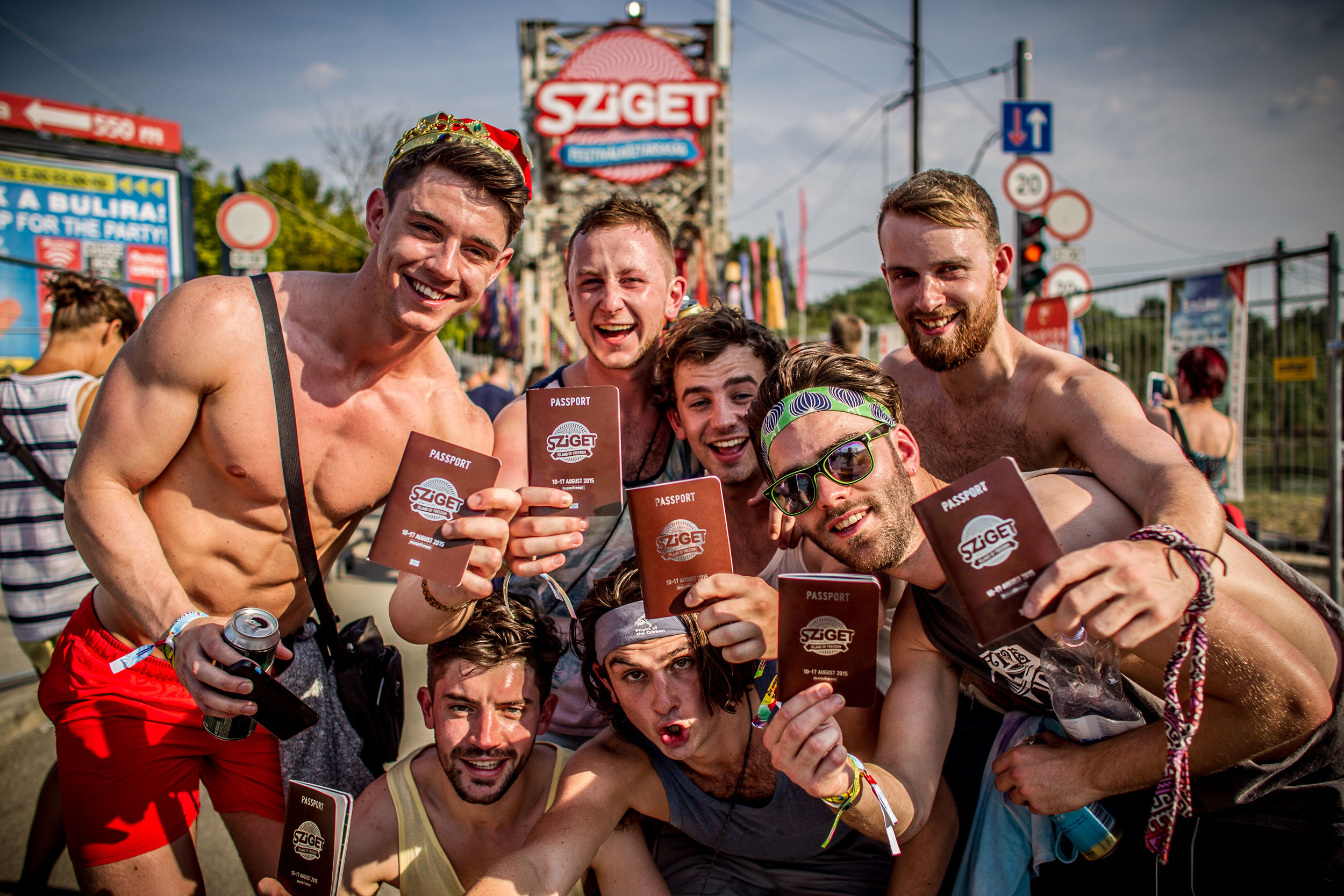 Men hold up their Sziget passports