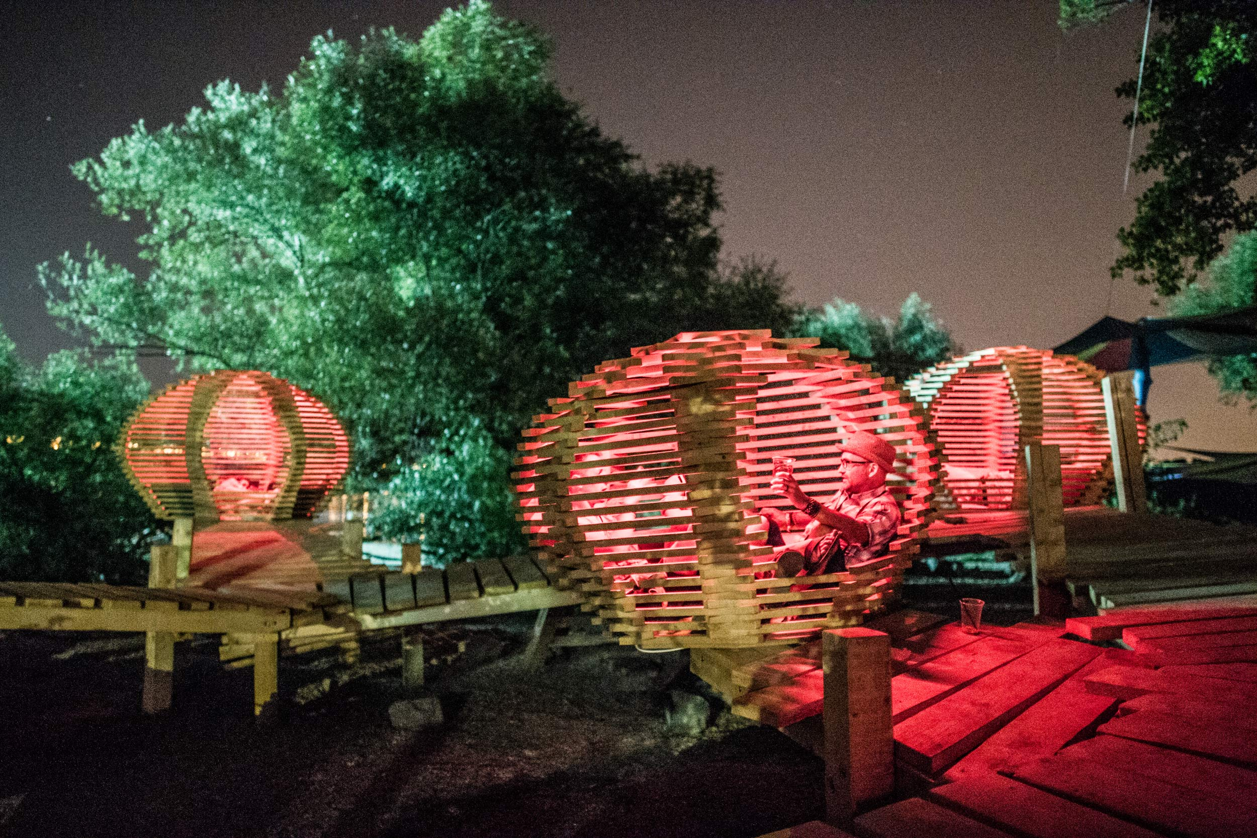 People relax in wooden cocoons