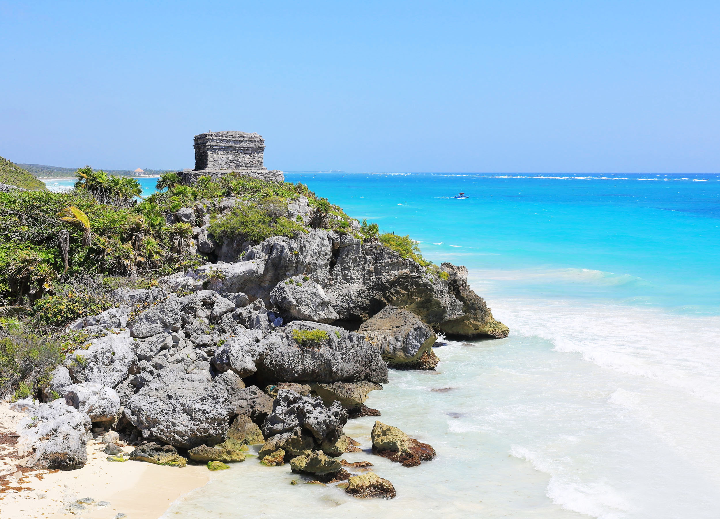 A stone rectangular building on arocky outcrop, God of the Winds temple in Tulum, Mexico