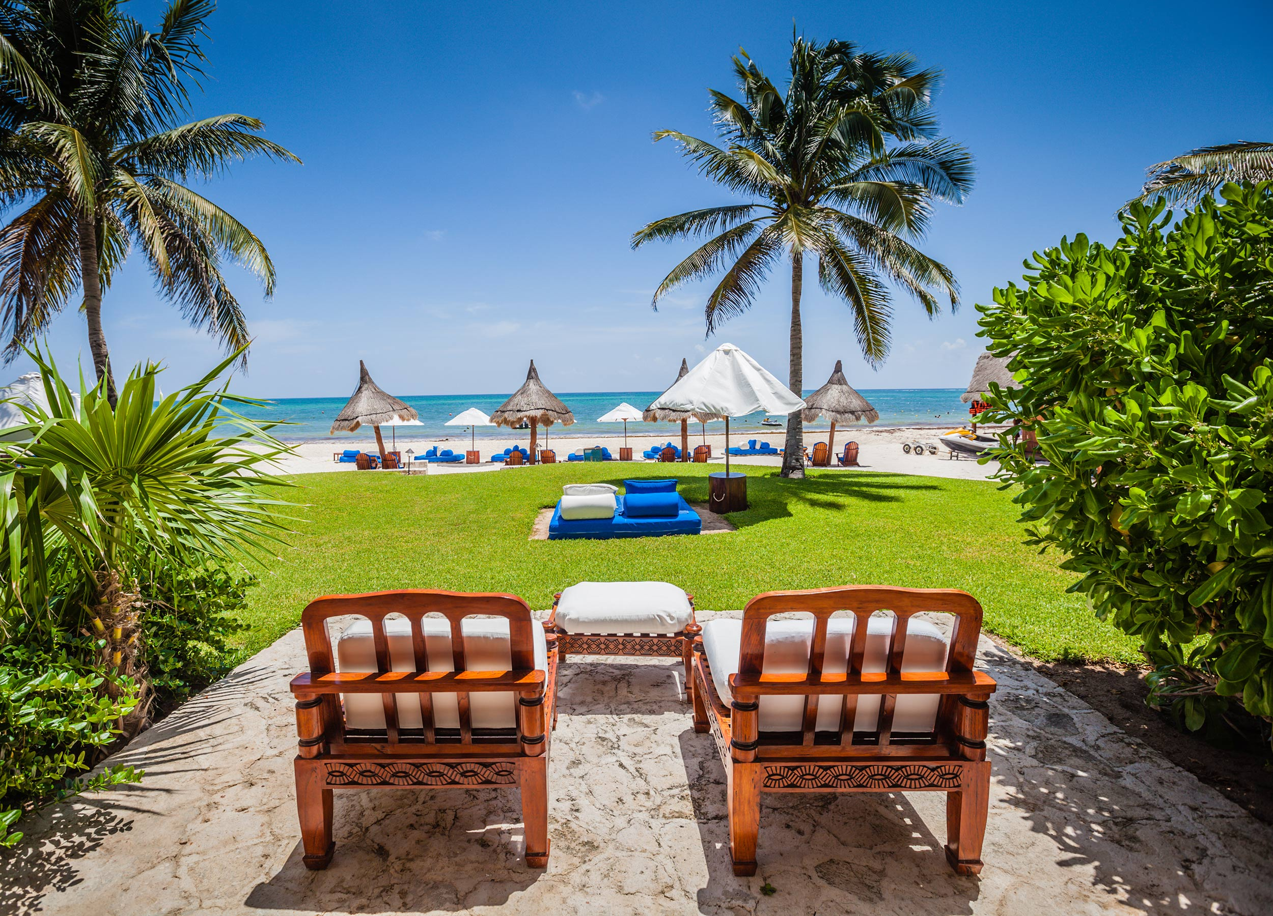 Two wooden chairs looking out to the umbrellas and loungers on the beach, Belmond Maroma in the Yucatan.
