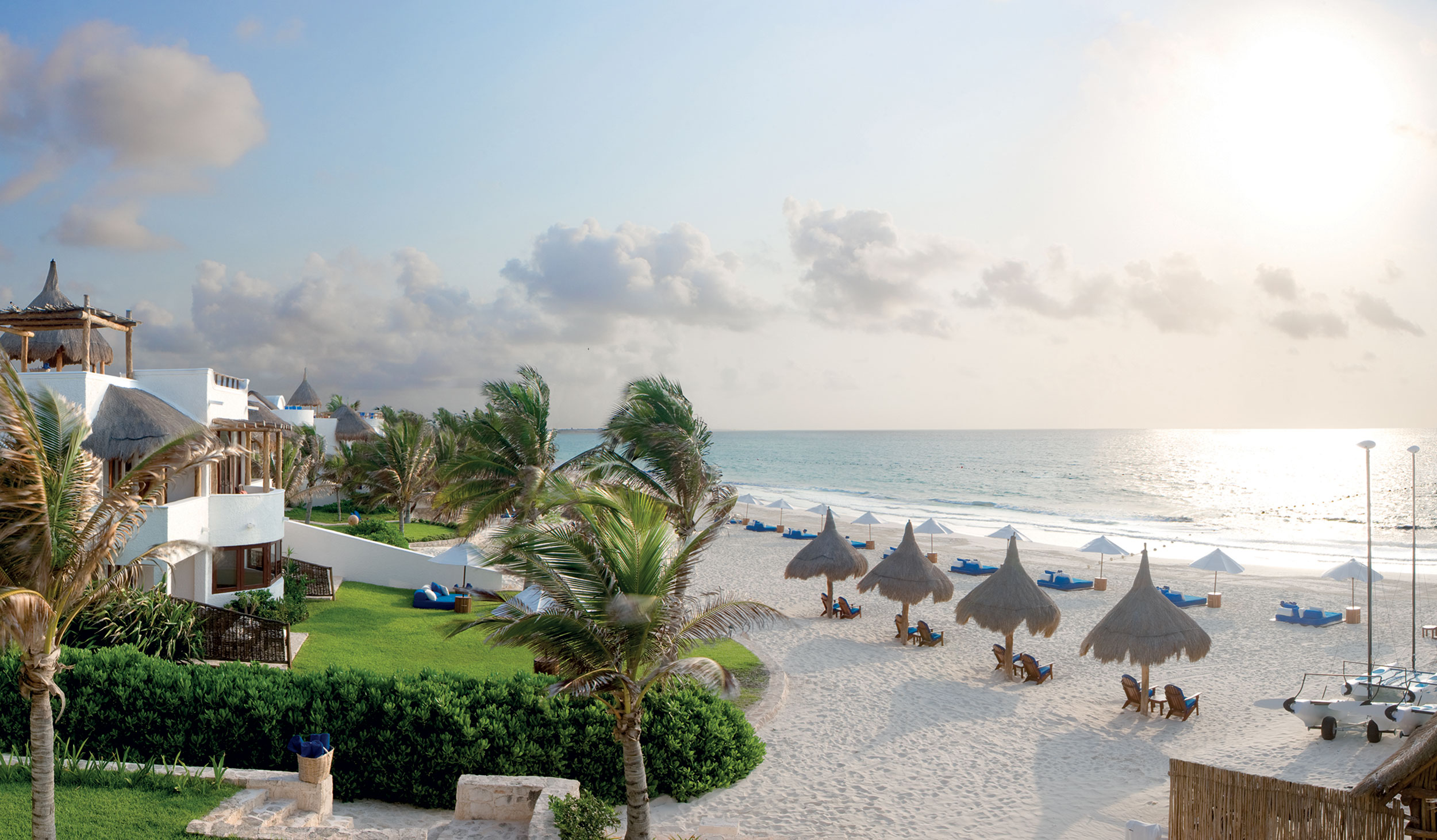 Beach view of umbrellas and loungers on the beach at sunset, Belmond Maroma