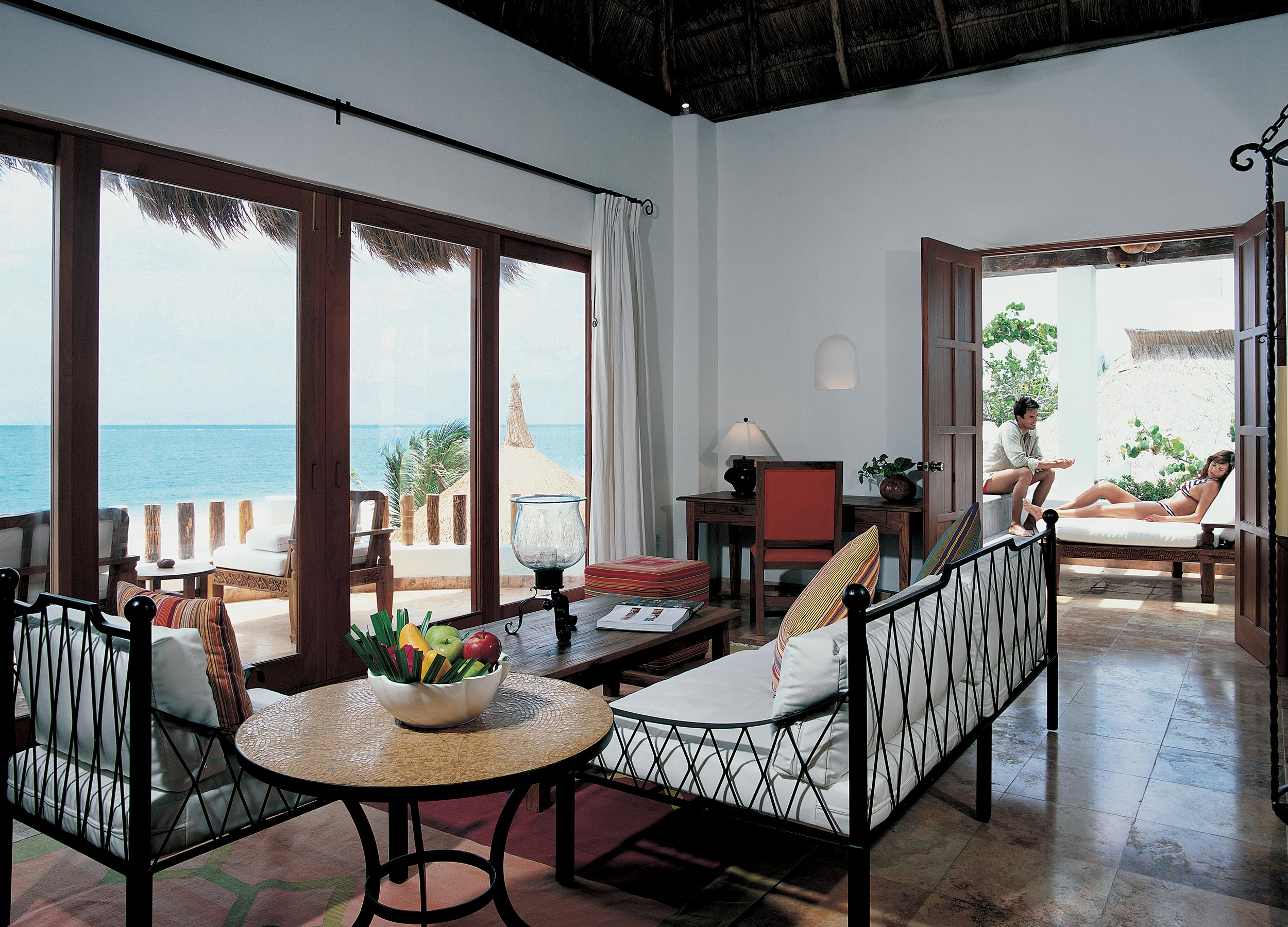View through a living area out to the balcony and the sea at Belmond Maroma, Yucatan