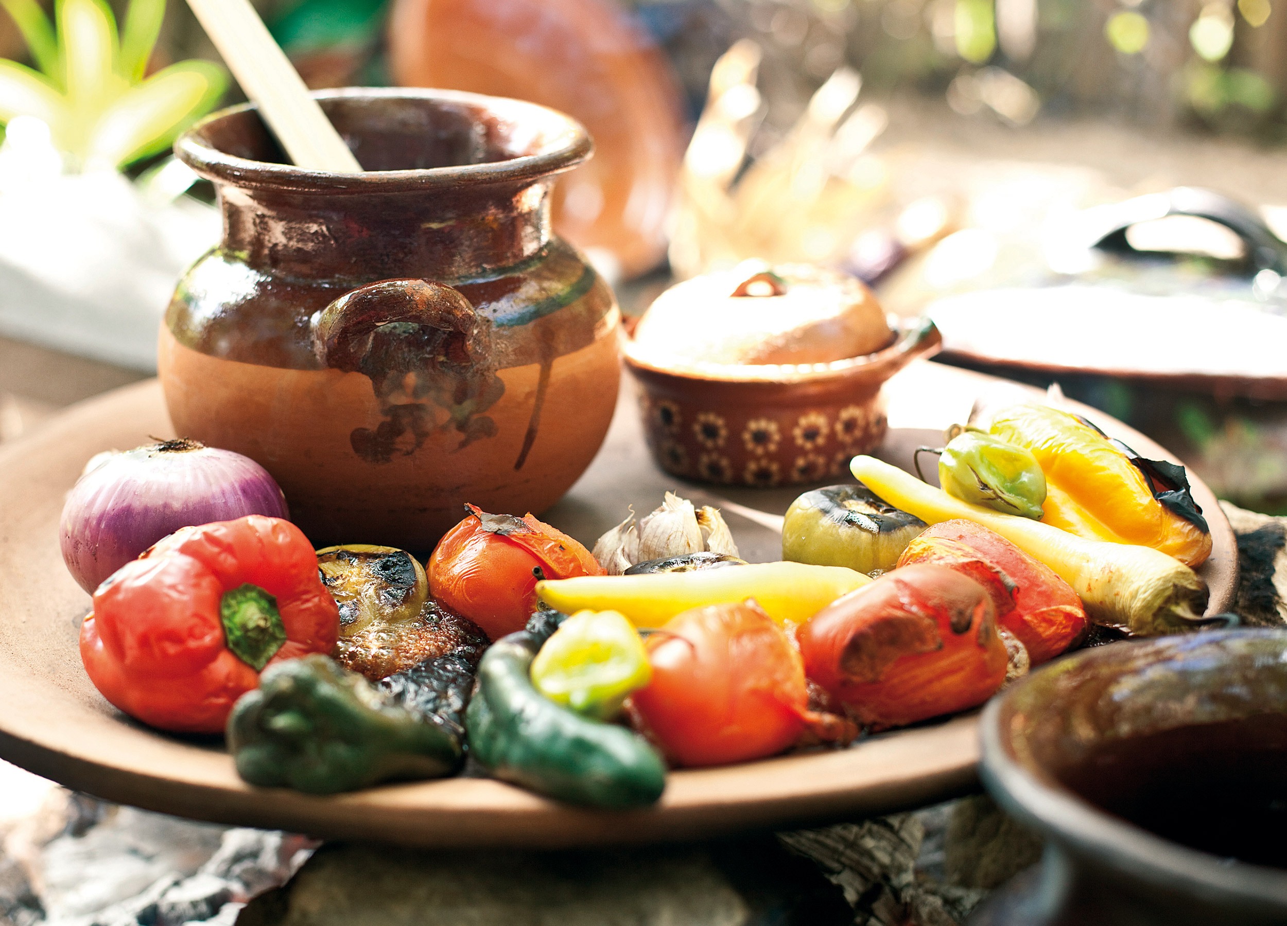 Roast vegetables and condiments in bowls on a platter, Mexico