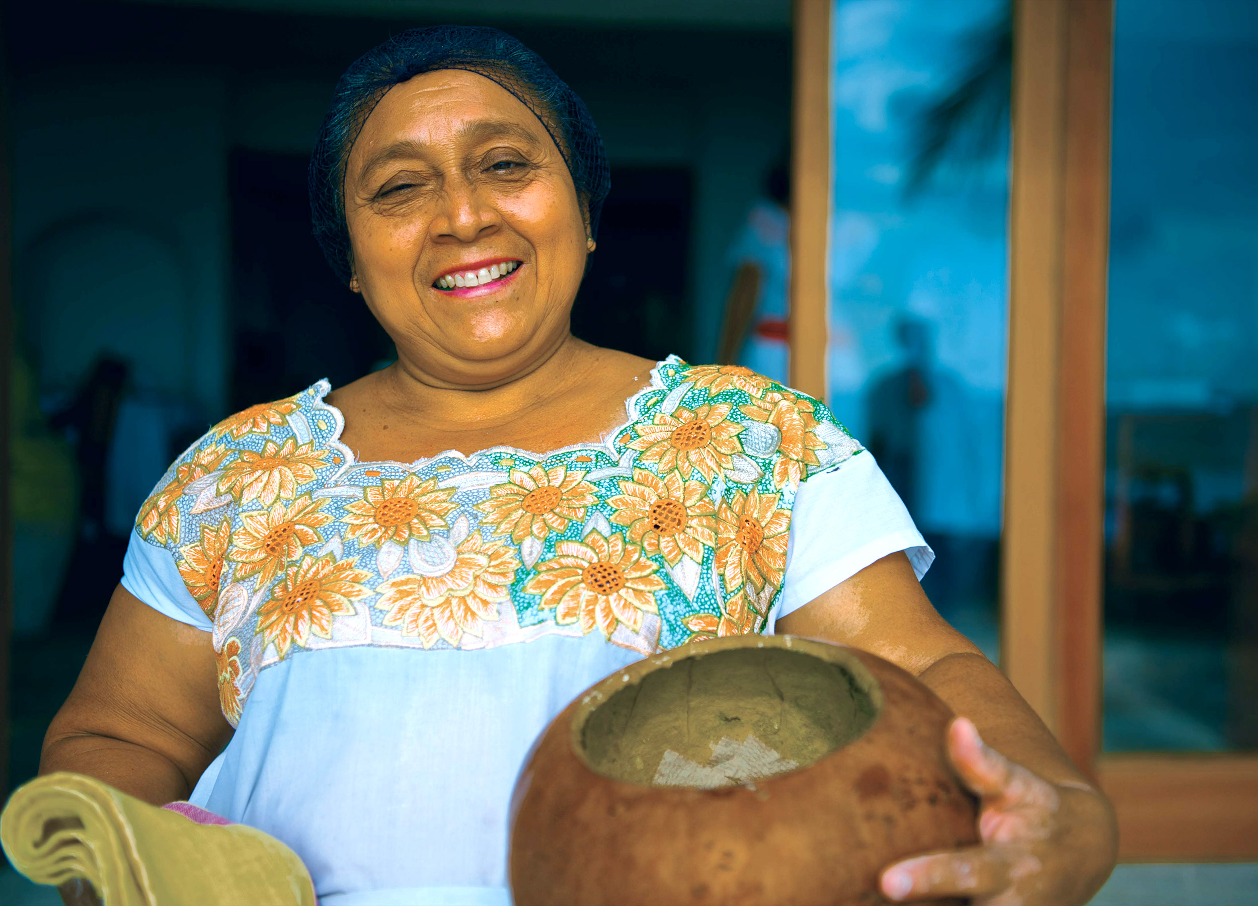 A smiling lady in a headscarf and blue dress holding a wooden pot at Belmond Maroma in Mexico