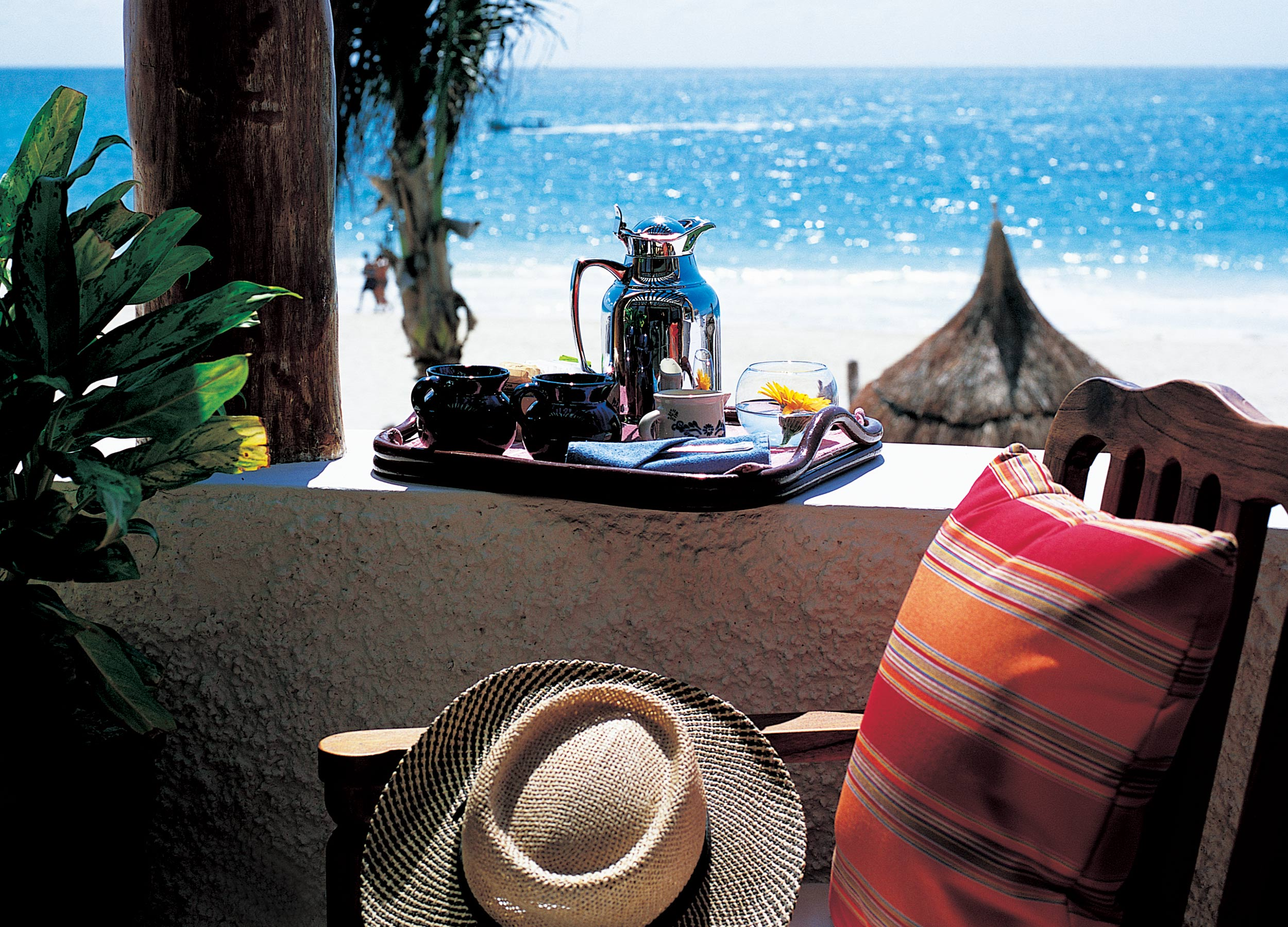 A straw hat on a cushioned chair with a tea service tray on the wall overlooking the sea