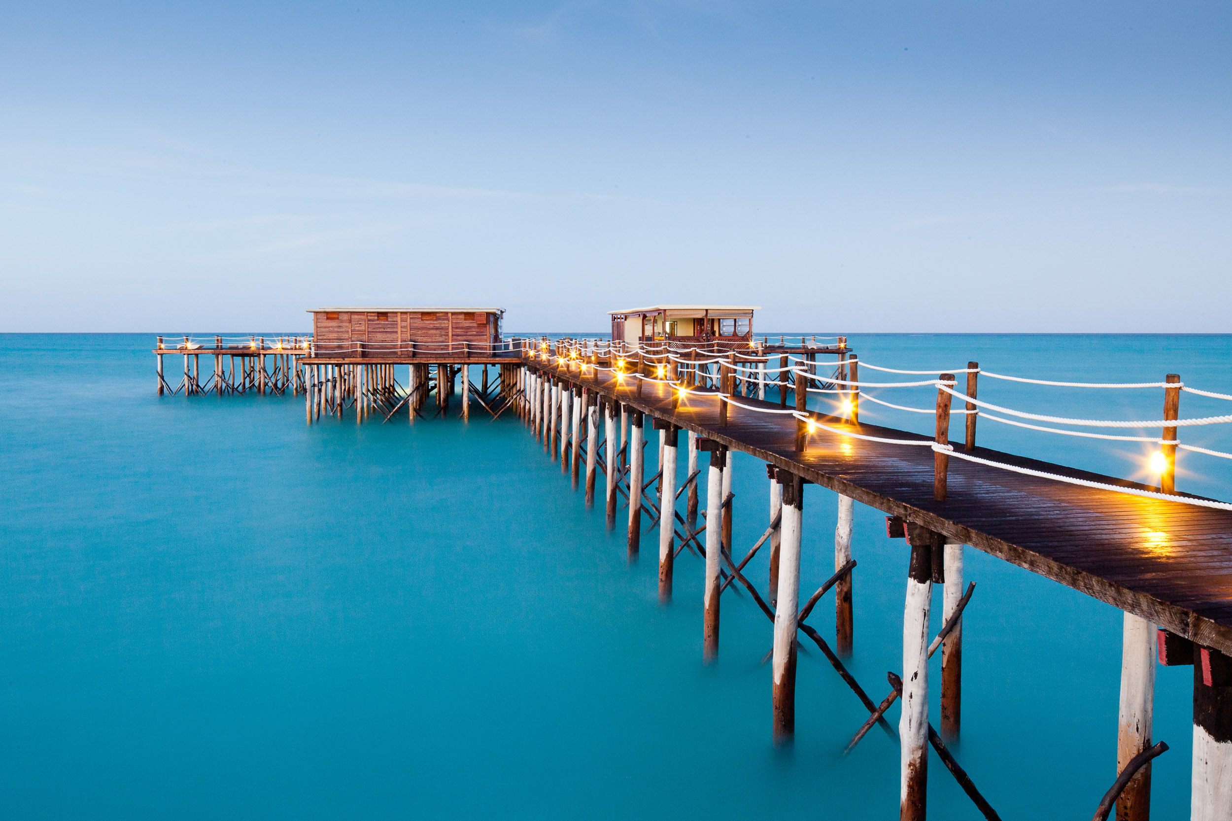 A long light-strung boardwalk jetty in the ocean at Essque Zalu Zanzibar