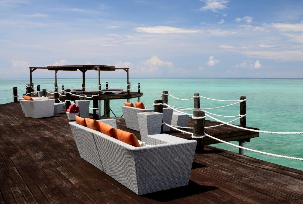 Couches with orange cushions on a wooden jetty facing the ocean at Essque Zalu Zanzibar