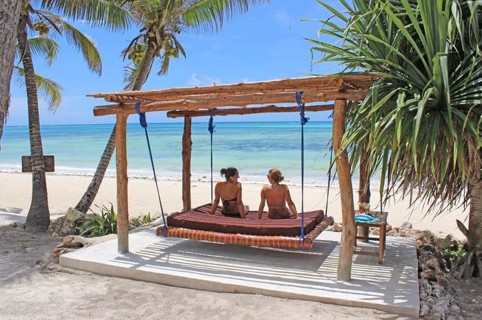 Two women on a traditional suspended daybed looking out to the sea at Boutique Hotel Matlai, Zanzibar