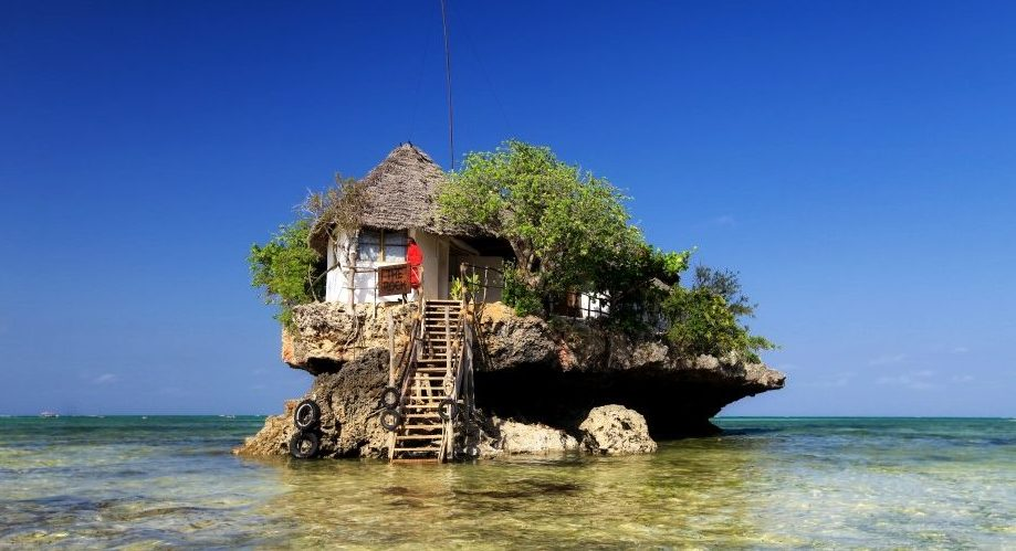 Thatched restaurant building on a rock with steps leading up to it in Zanzibar